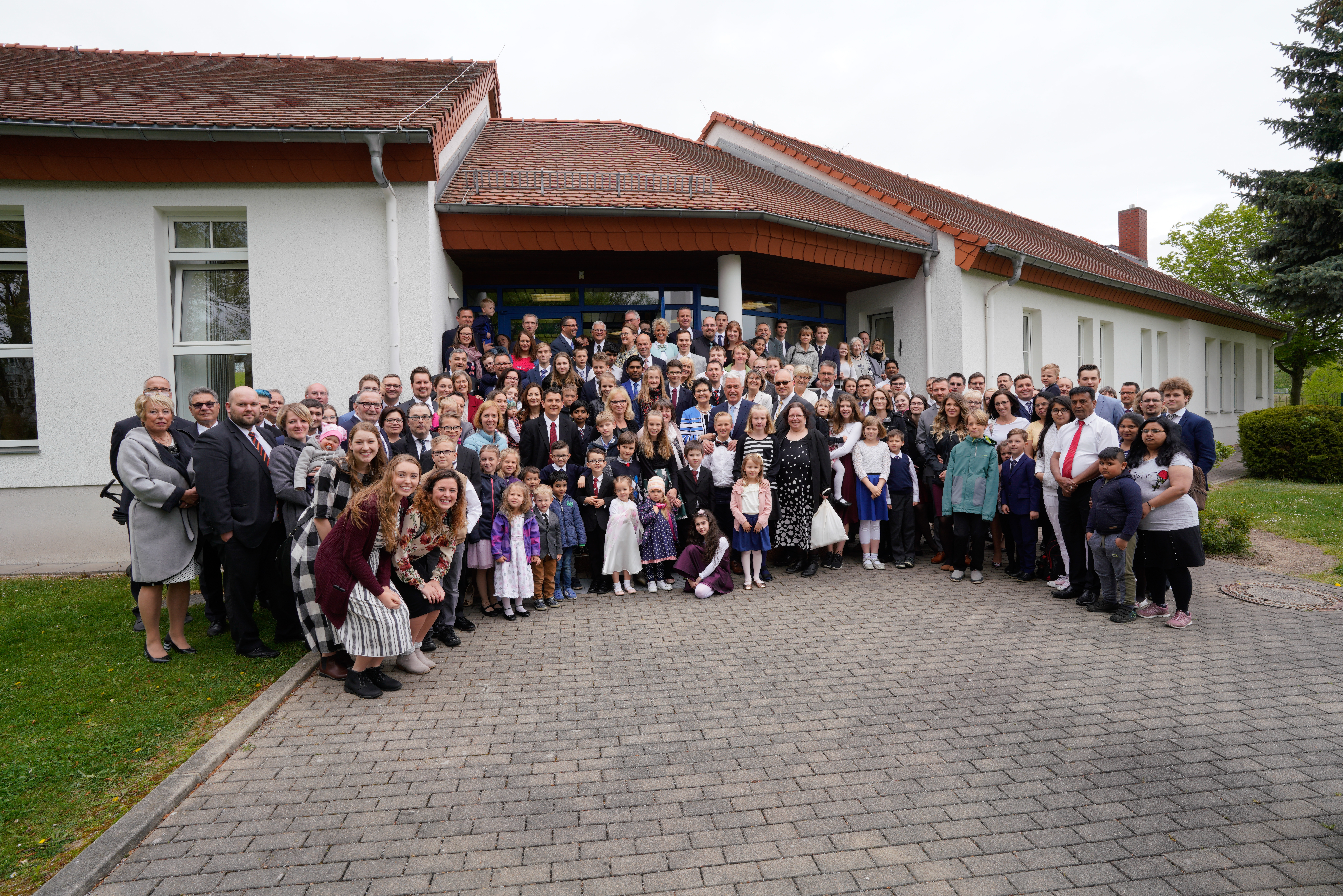 Elder Dieter F. Uchtdorf and Sister Harriet Uchtdorf, center, join members of the Görlitz Branch and visitors for a photograph after Sunday meetings in front of the meetinghouse on April 28, 2019, in Görlitz, Germany. The branch is commemorating its 120th year of existence.