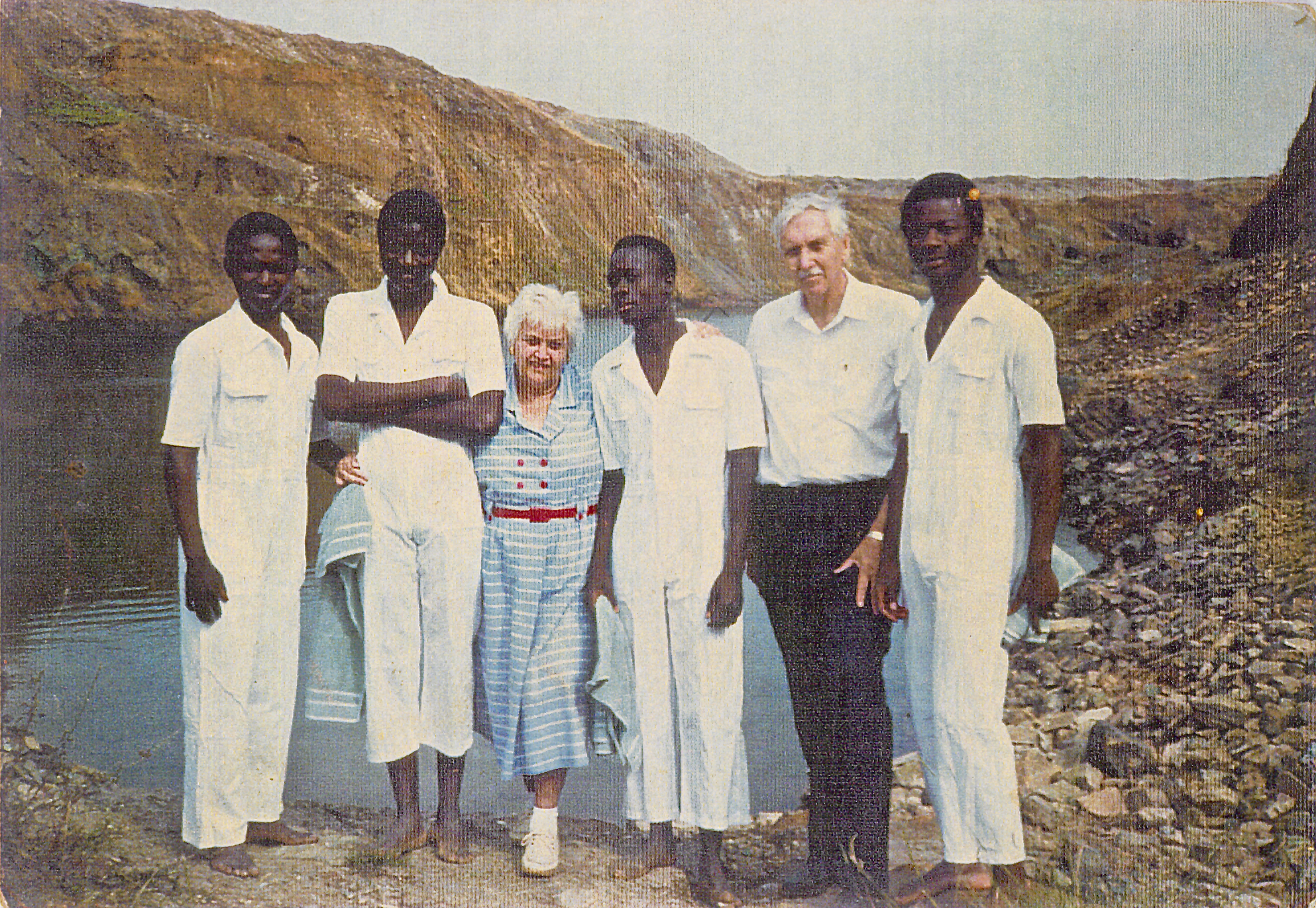 Church member Gilbert Mingtoyi, left, assists with the baptism of three men at the edge of an abandoned copper mine near Lubumbashi, Zaire, in 1987. Elder Arie Noot and Sister Ante Noot are the senior missionaries in the photo. Mingtoyi had been baptized in May 1987 at the same location as a part of baptismal service involving 80 converts.