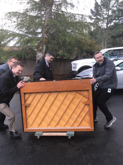 Missionaries help with the delivery of a piano to new owners.