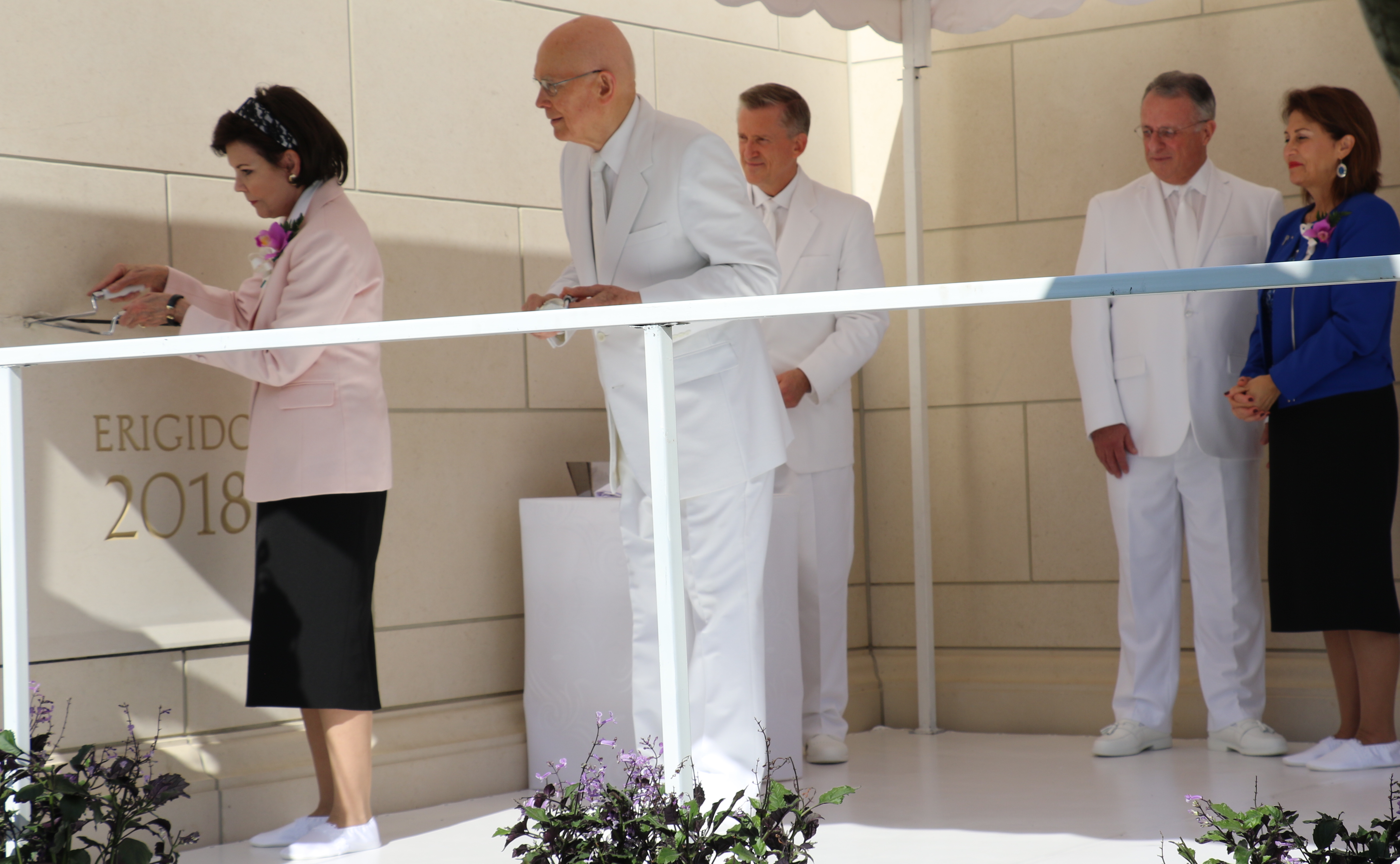 Sister Kristen Oaks, left, places some mortar on the temple capstone under the watch of her husband, President Dallin H. Oaks of the First Presidency during the Sunday, Nov. 9, 2018, dedication of the Barranquilla Colombia Temple. At right are Elder Ulisses Soares and his wife, Sister Rosana Soares.