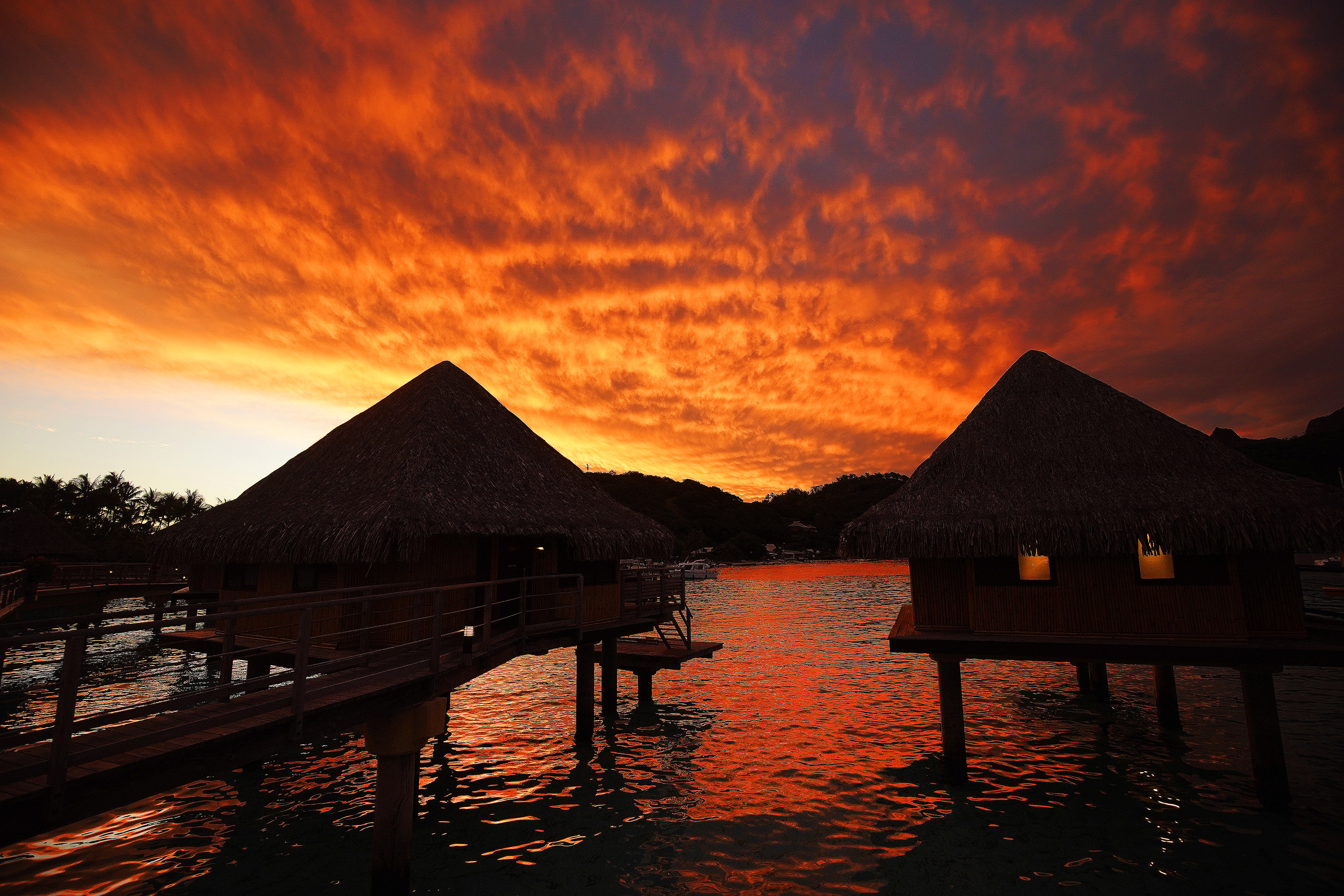 Overwater bungalows are silhouetted in Bora Bora on May 28, 2019.