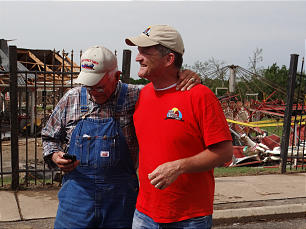 Glenn Orr, left, and his son, Tom Orr, members of the Moore Ward, Oklahoma City South Stake, stand outside their family farm that was severely damaged by a tornado on May 20.