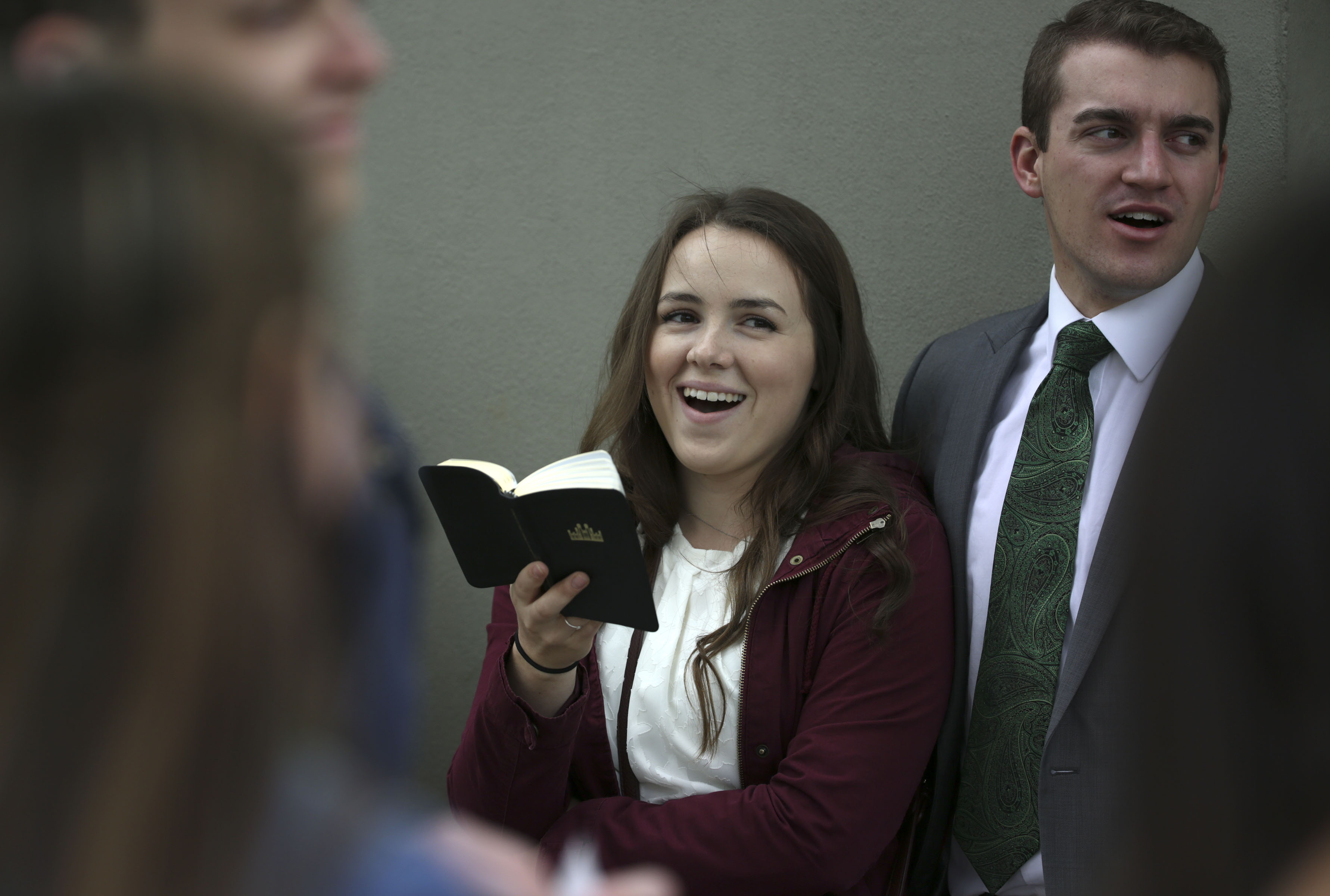 Ariana Halbeisen and Jordan Harlan sing hymns with other members of the Logan Young Single Adults First Stake between sessions of the 188th Semiannual General Conference of The Church of Jesus Christ of Latter-day Saints outside of Temple Square in downtown Salt Lake City on Sunday, Oct. 7, 2018.