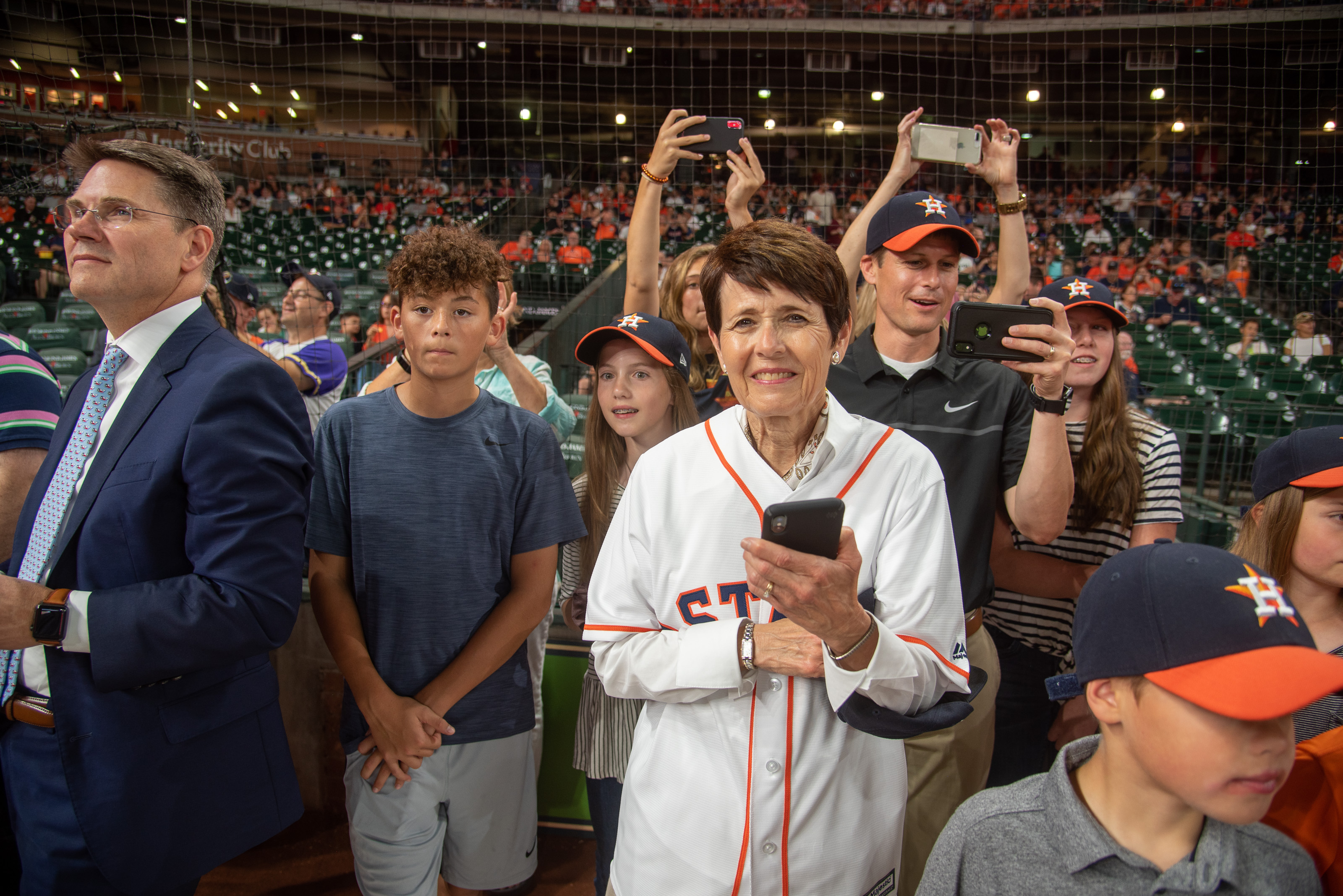 Sister Susan Bednar, with her family, waits as Elder David A. Bednar walks to the pitchers' mound.