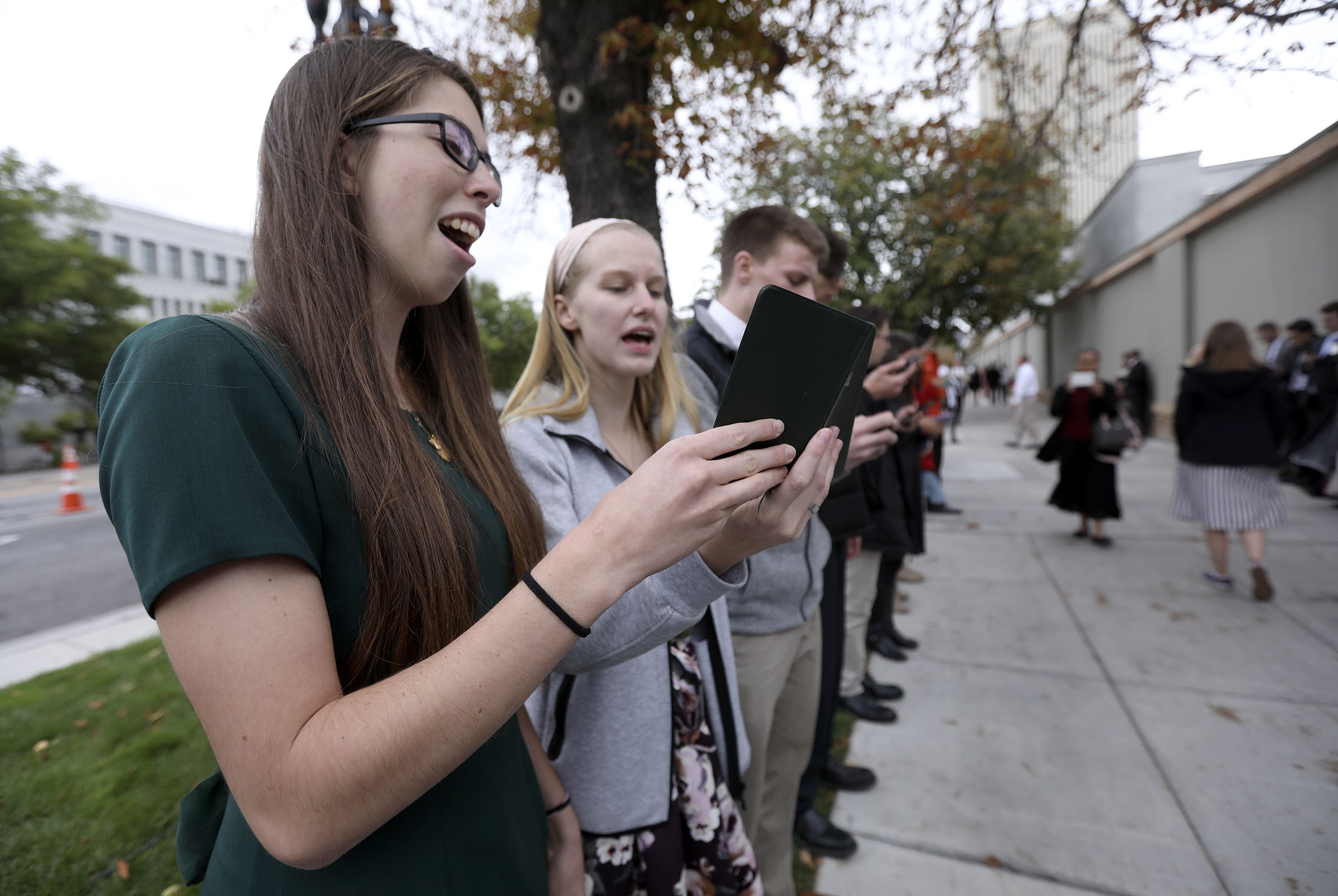 Rebecca Sherrill and Ryan Aust sing hymns with other members of the Logan Young Single Adults First Stake between sessions of the 188th Semiannual General Conference of The Church of Jesus Christ of Latter-day Saints outside of Temple Square in downtown Salt Lake City on Sunday, Oct. 7, 2018.