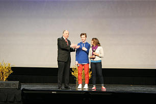 """Elder Neil L. Andersen applauds Micah Rindlisbacher and Tia Thompson after their perfomance of """"Find Our Cousins,"""" composed expressly for the occasion, the devotional of Youth Family Discovery Day at RootsTech 2014."""