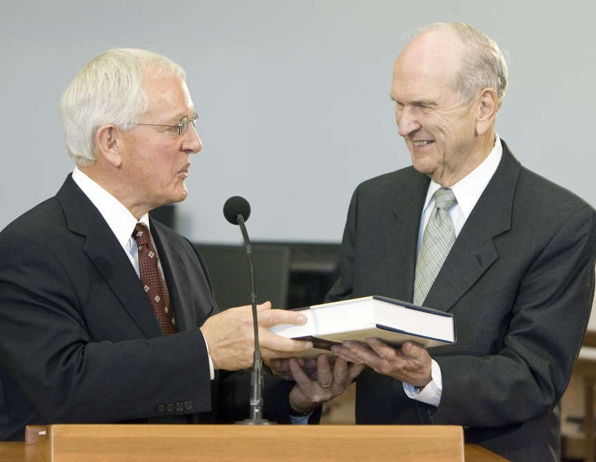 Elder Marlin K. Jensen presents a copy of a Joseph Smith Papers volume to Elder Russell M. Nelson of the Quorum of the Twelve Apostles during a press conference in 2009.