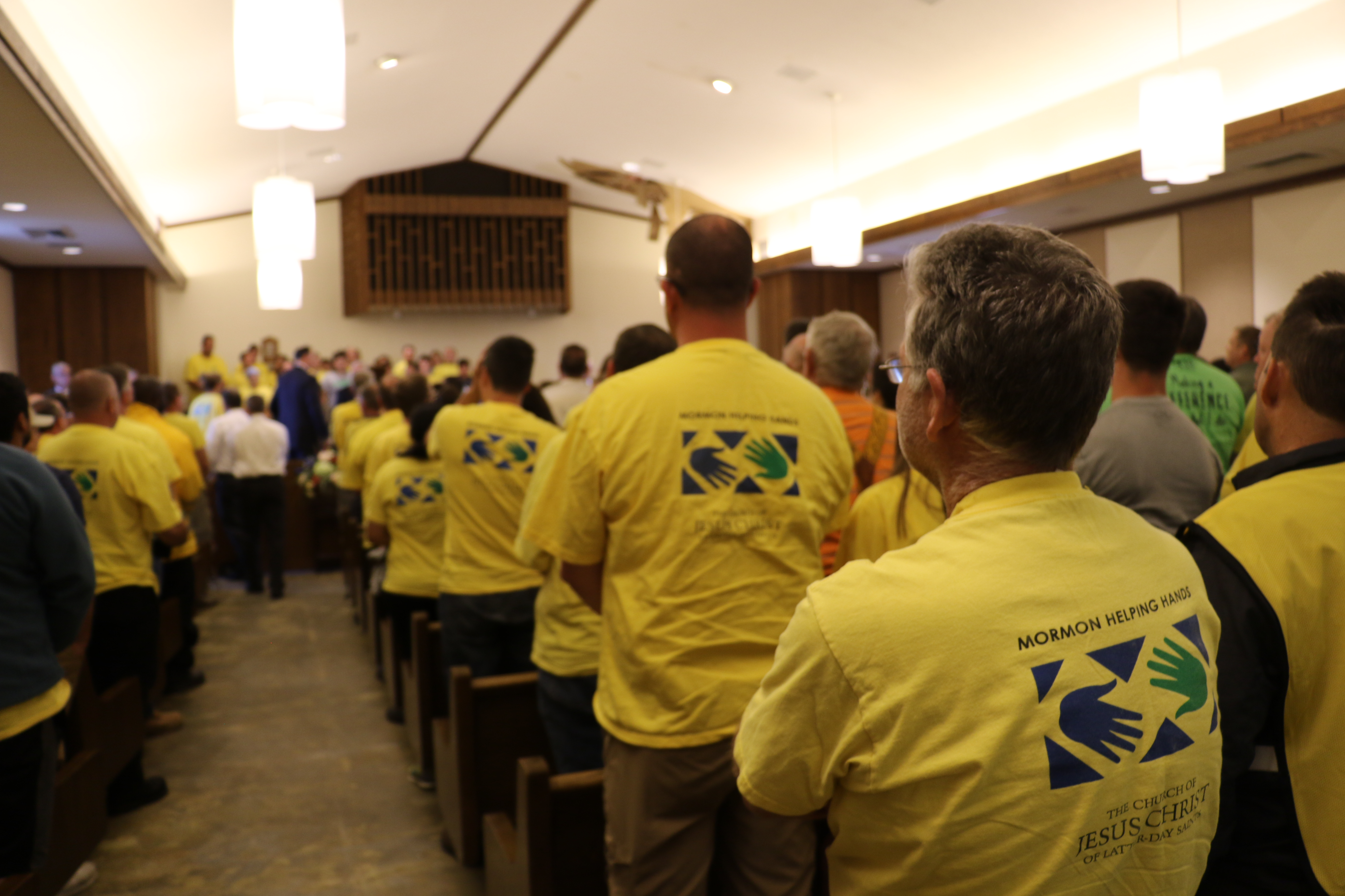 Yellow-clad Helping Hands volunteers come to their feet as President Dallin H. Oaks of The Church of Jesus Christ of Latter-day Saints and other visiting leaders arrive for early morning Sunday service in Panama City, Florida, on Oct. 21, 2018.