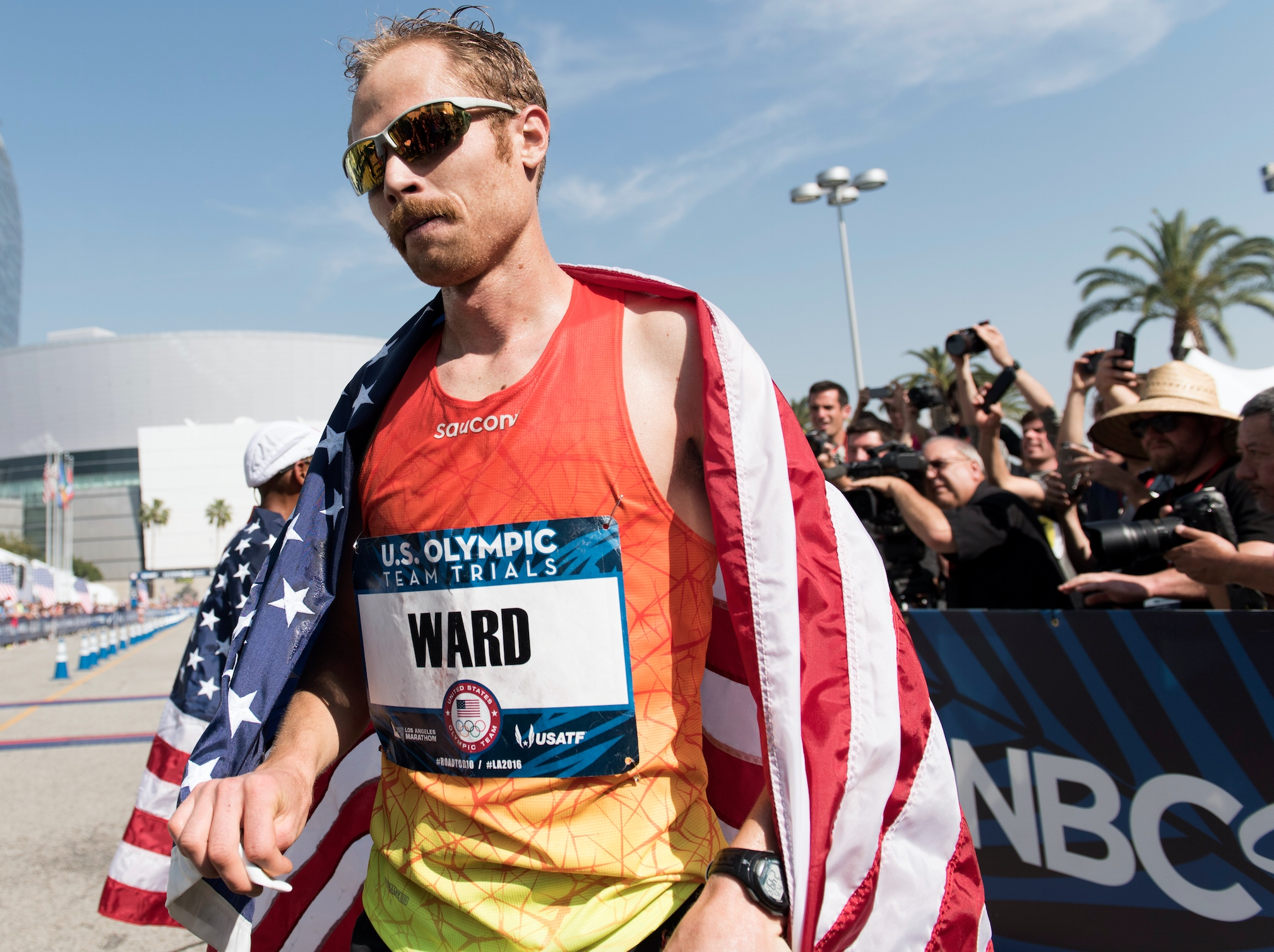 Jared Ward walks from the finish line with a United States Flag on his back during the U.S. Olympic marathon trials, Saturday, Feb. 13, 2016, in Los Angeles.