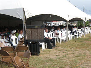 Members unable to enter the Spanish Town meetinghouse watch proceedings on a large video display. Erected to shield conferencegoers from the Caribbean sun, the crowd under the tent also exceeded its 600-person capacity.