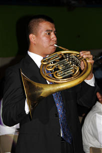A young musician sounds the horn signaling the start of the Aug. 20 cultural celebration held at San Salvador's National Gymnasium.