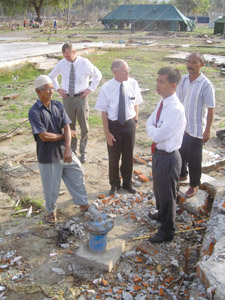Elder Subandriyo, front right, and Elder Thomas Palmer, middle, view damage in Indonesia after tsunami.