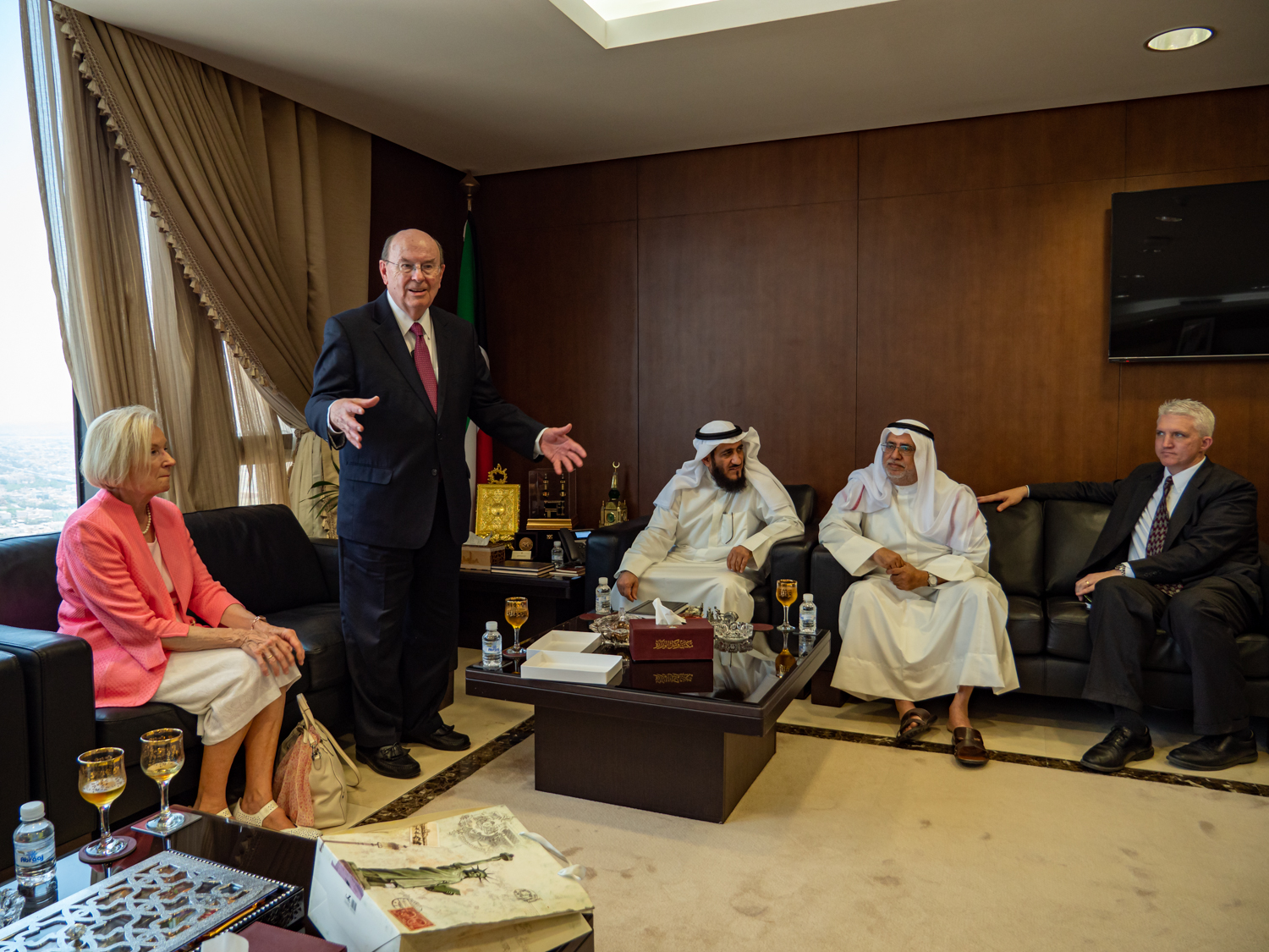 Elder Quentin L. Cook speaks in a meeting with Mr. Fareed Emadi, secretary general of the Supreme Commission for the Promotion of Moderation in the Ministry of Awqaf, middle, and others in Kuwait City on June 10, 2019. Sister Mary Cook is at left.