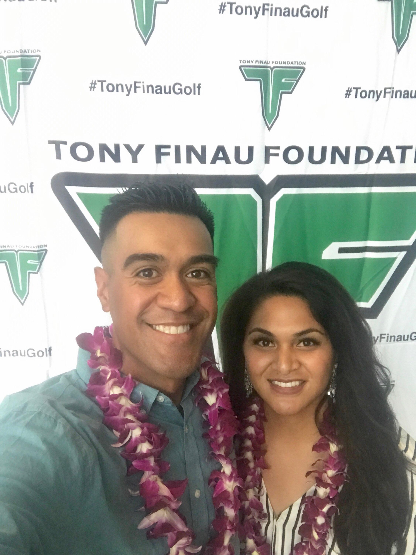 Tony Finau and Alayna Finau pose for a photo by a Tony Finau Foundation backdrop.