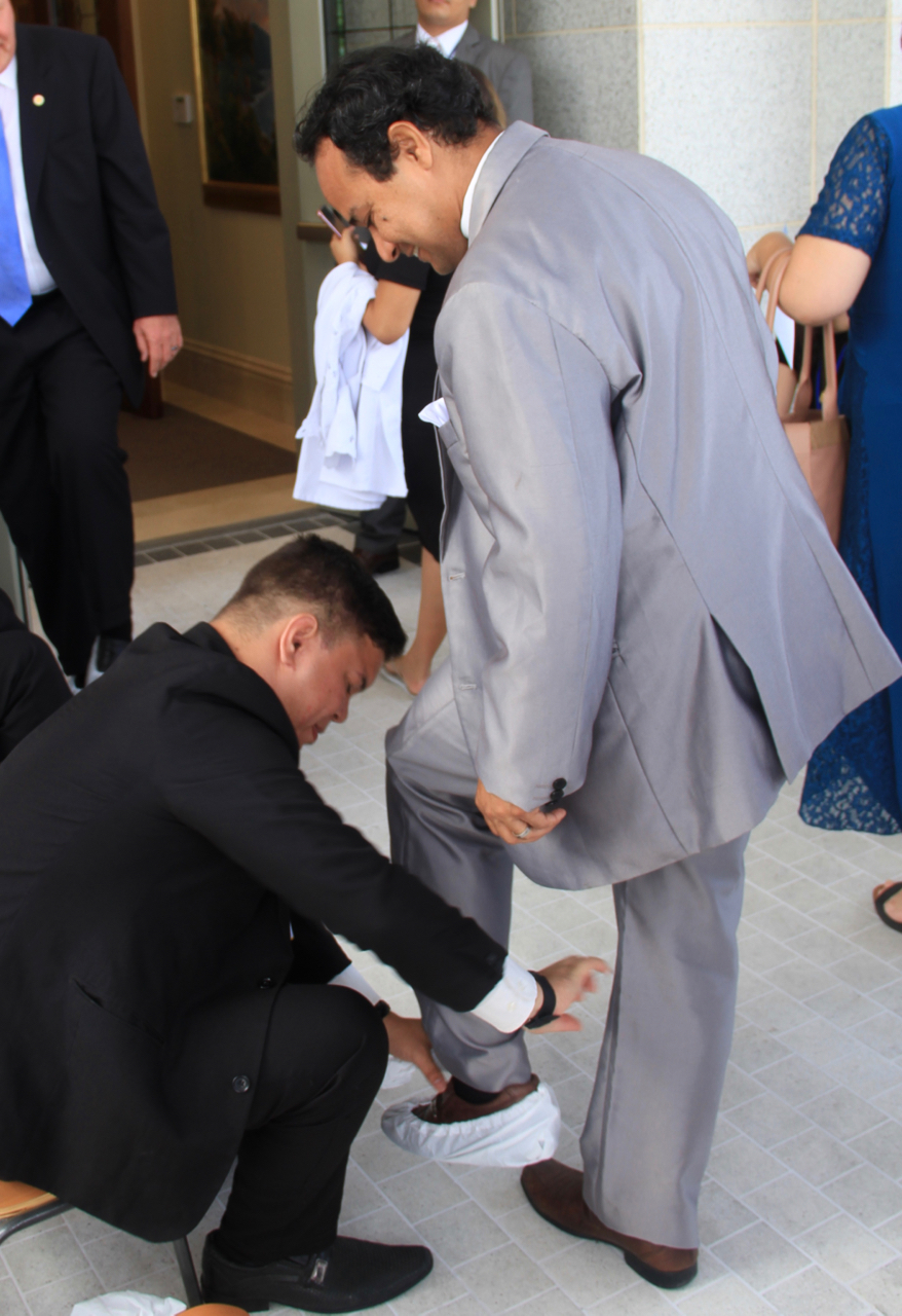 Volunteers place protective coverings on the shoes of dedication session attendees prior to the dedication of the Fortaleza Brazil Temple on Sunday, June 2, 2019.