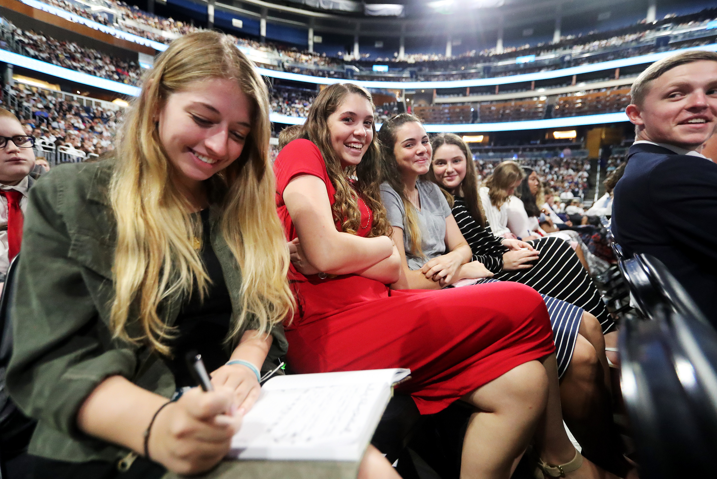 A group of young women sit at a devotional with President Russell M. Nelson and others at the Amway Center in Orlando, Florida, on Sunday, June 9, 2019.