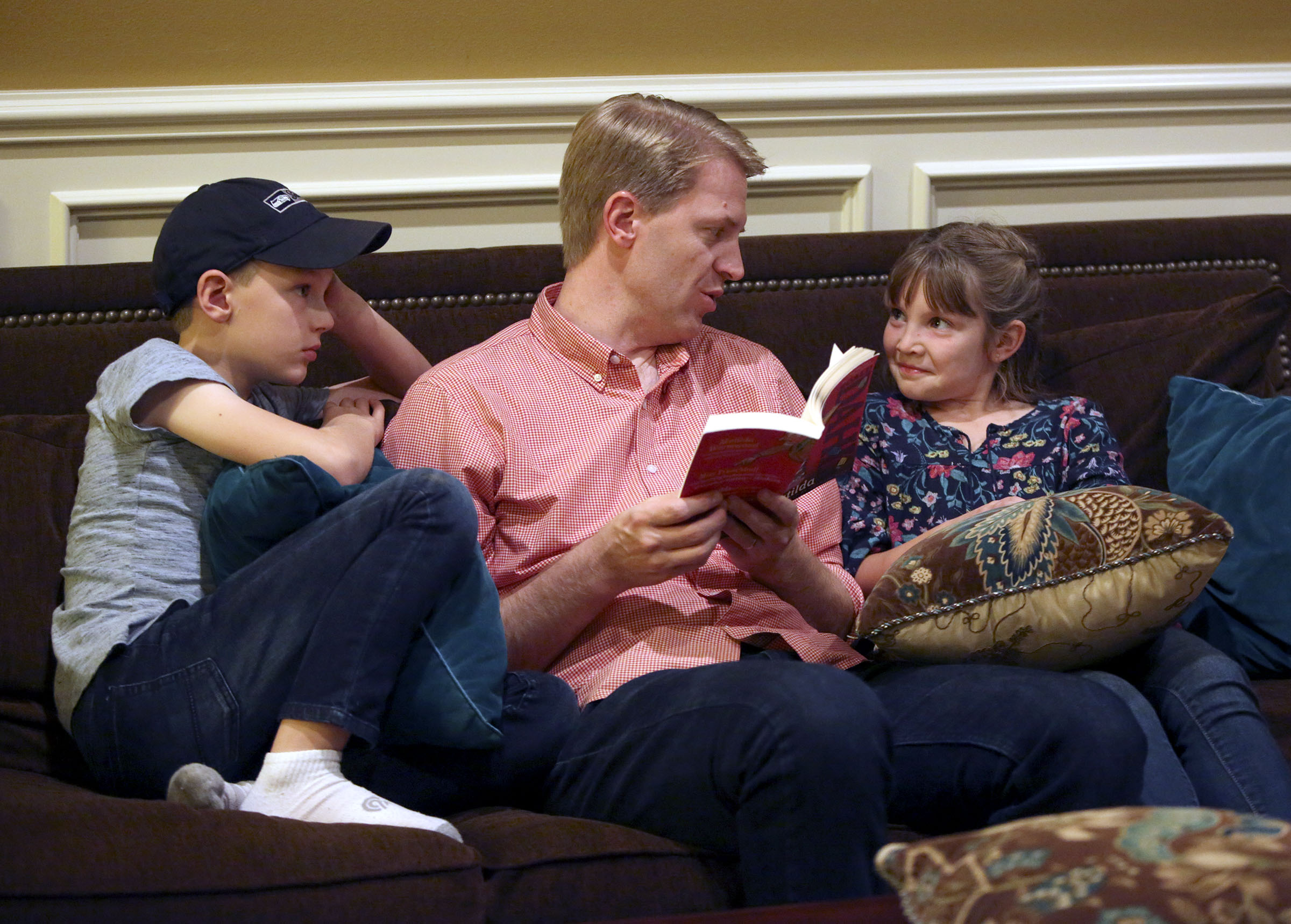 Justin Allen, center, reads to his son Tom Allen and daughter Emilia Allen at home in Renton, Wash., on Friday, Sept. 14, 2018.