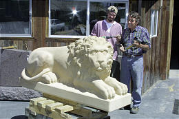 John and Hans Huettlinger observe lion they carved to replace original at Lion House, shown on portico below, in early photo.