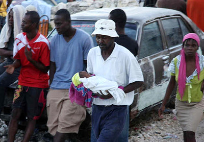 In this image made available by the American Red Cross in London, Wednesday Jan. 13, an earthquake survivor carries a small baby in a shanty town on the outskirts of Port au Prince, following a major earthquake in Haiti, Tuesday Jan. 12, 2010.