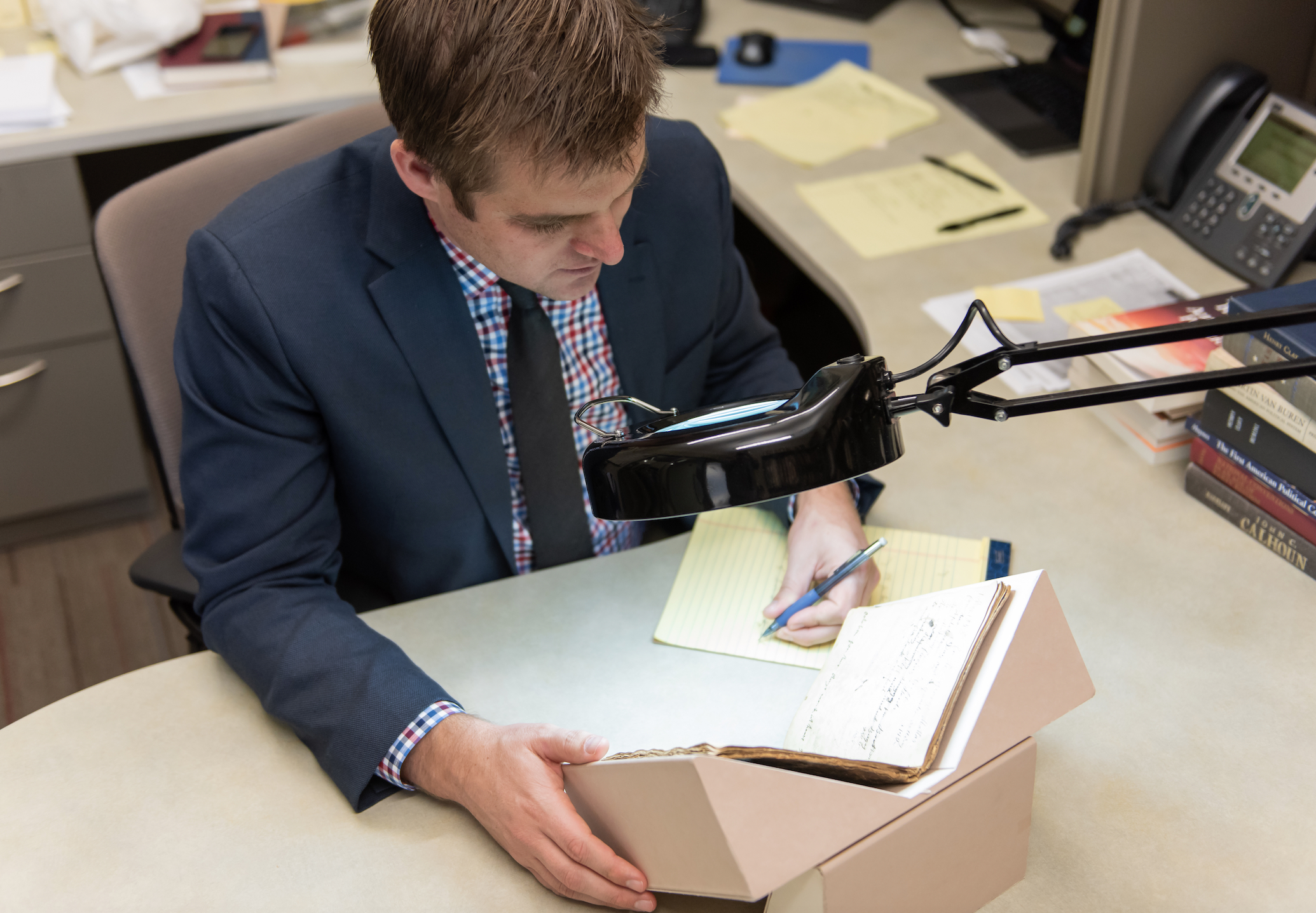 Historian Spencer W. McBride uses an illuminated magnifier to examine a journal from the early 1800s.