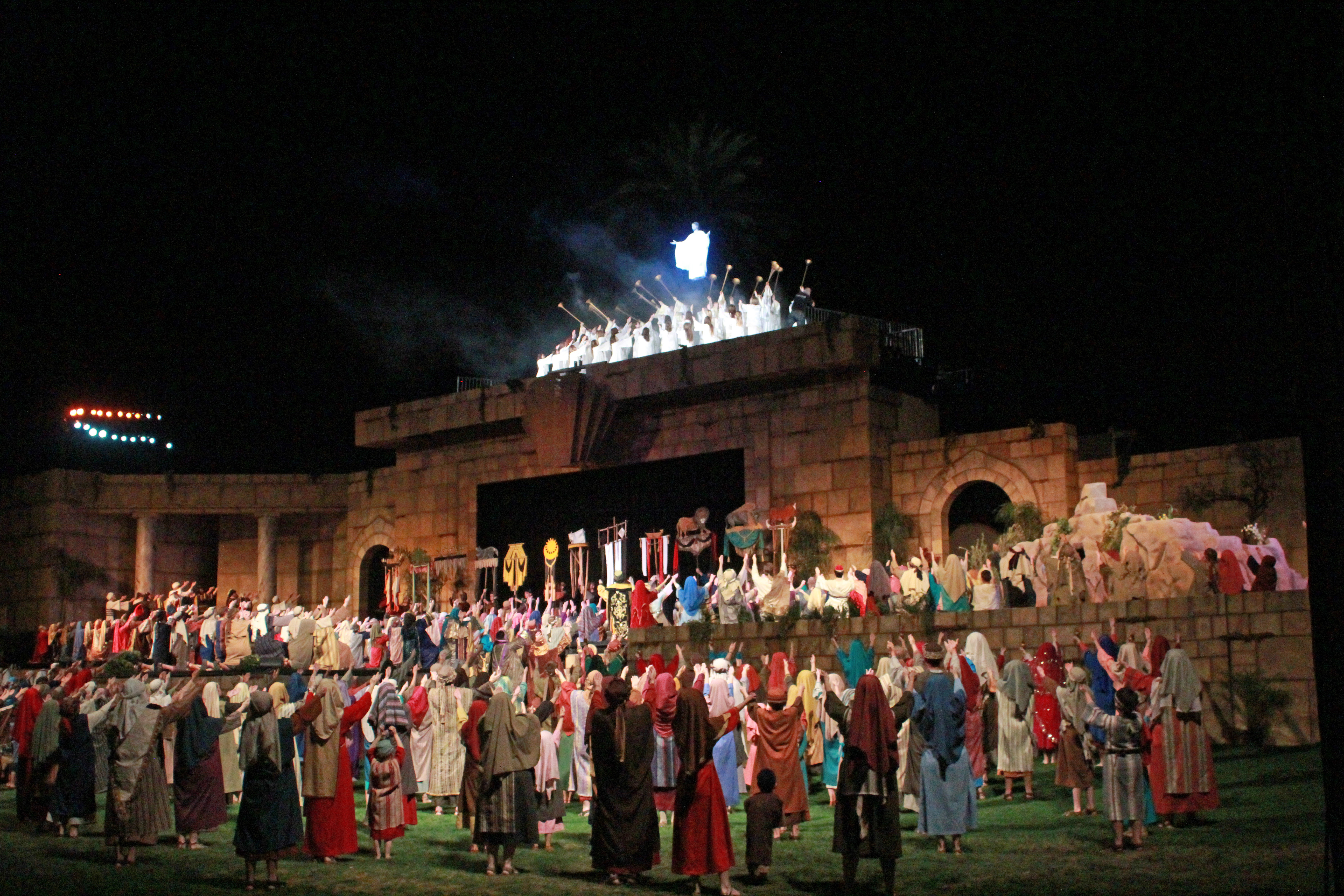 """Cast members fill the stage and the grassy area in front while singing """"I know He lives!"""" during the finale of the Mesa Easter Pageant."""