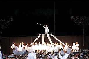 In the final moments of The Gila Valley Arizona Temple cultural celebration, 1,600 youth draped in white capes stand on the football field at Eastern Arizona College stadium and watch as a replica Angel Moroni is hoisted high into the air.