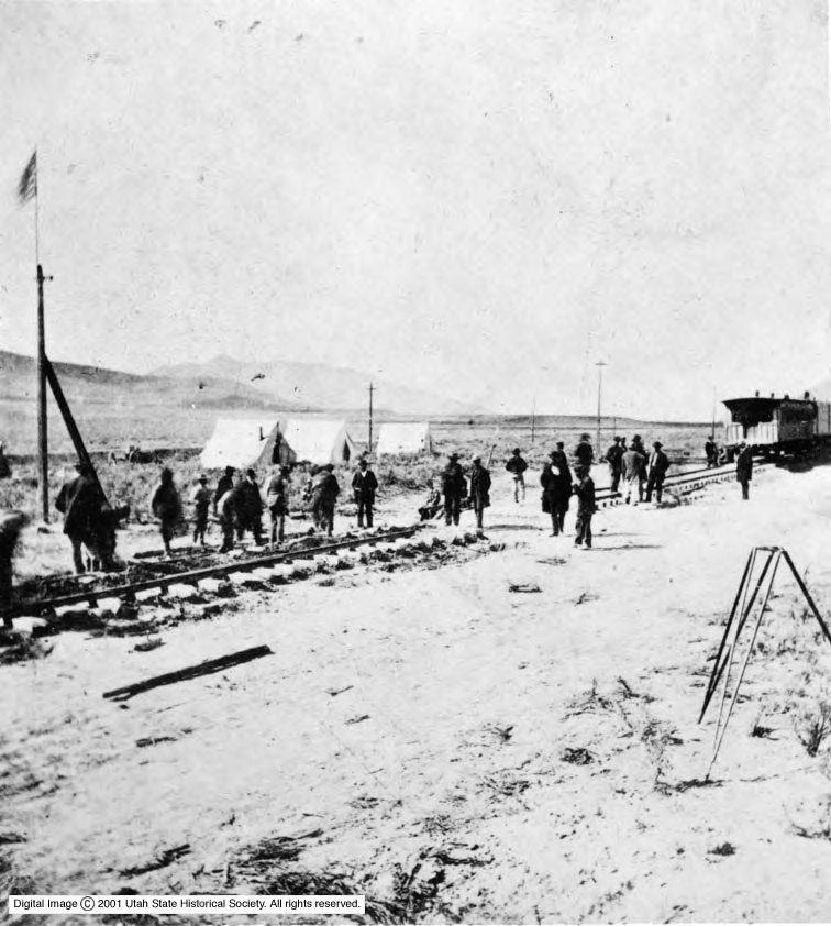 Individuals gather on the rails the morning before the laying of the last rail and the joining of the Union Pacific and Central Pacific railroads.