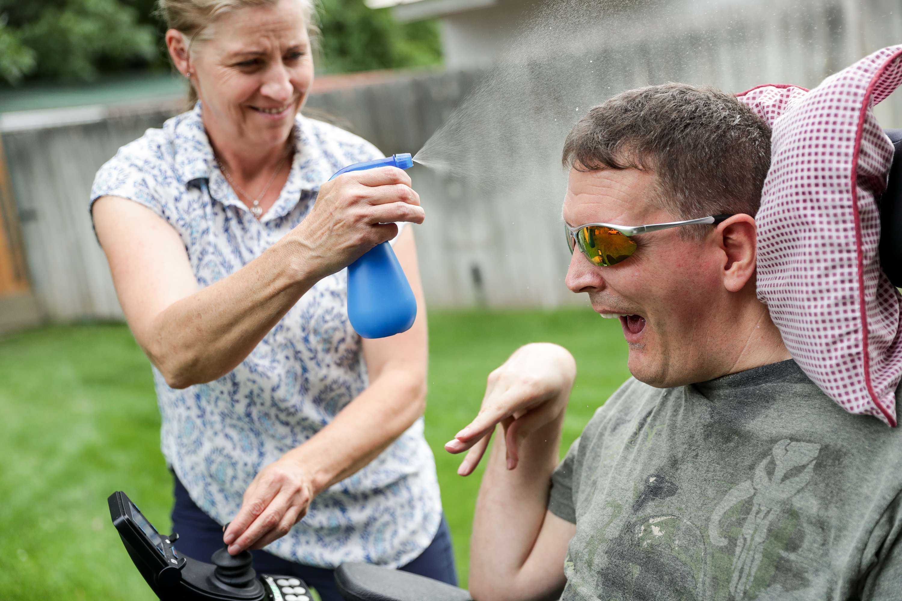 Orin Voorheis smiles as his caregiver, Wendy Tobey, sprays him with a mist of water while driving around in a motorized wheelchair at his home in Pleasant Grove, Utah, on Tuesday, July 10, 2018. Because Voorheis is unable to regulate his body temperature due to his brain injury, his caregivers must be careful to keep him cool when outside in heat.