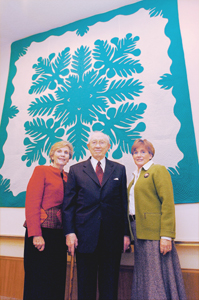 President Gordon B. Hinckley, with one of his daughters, Jane Dudley, right, and Relief Society General President Bonnie D. Parkin, stands in front of a Hawaiian quilt presented to the Relief Society in memory of Sister Marjorie Pay Hinckley, who died April 6. The quilt, which hangs in the Relief Society Building, was created with a traditional breadfruit design by sisters in Hawaii and given as a gift to President Hinckley in 1997.