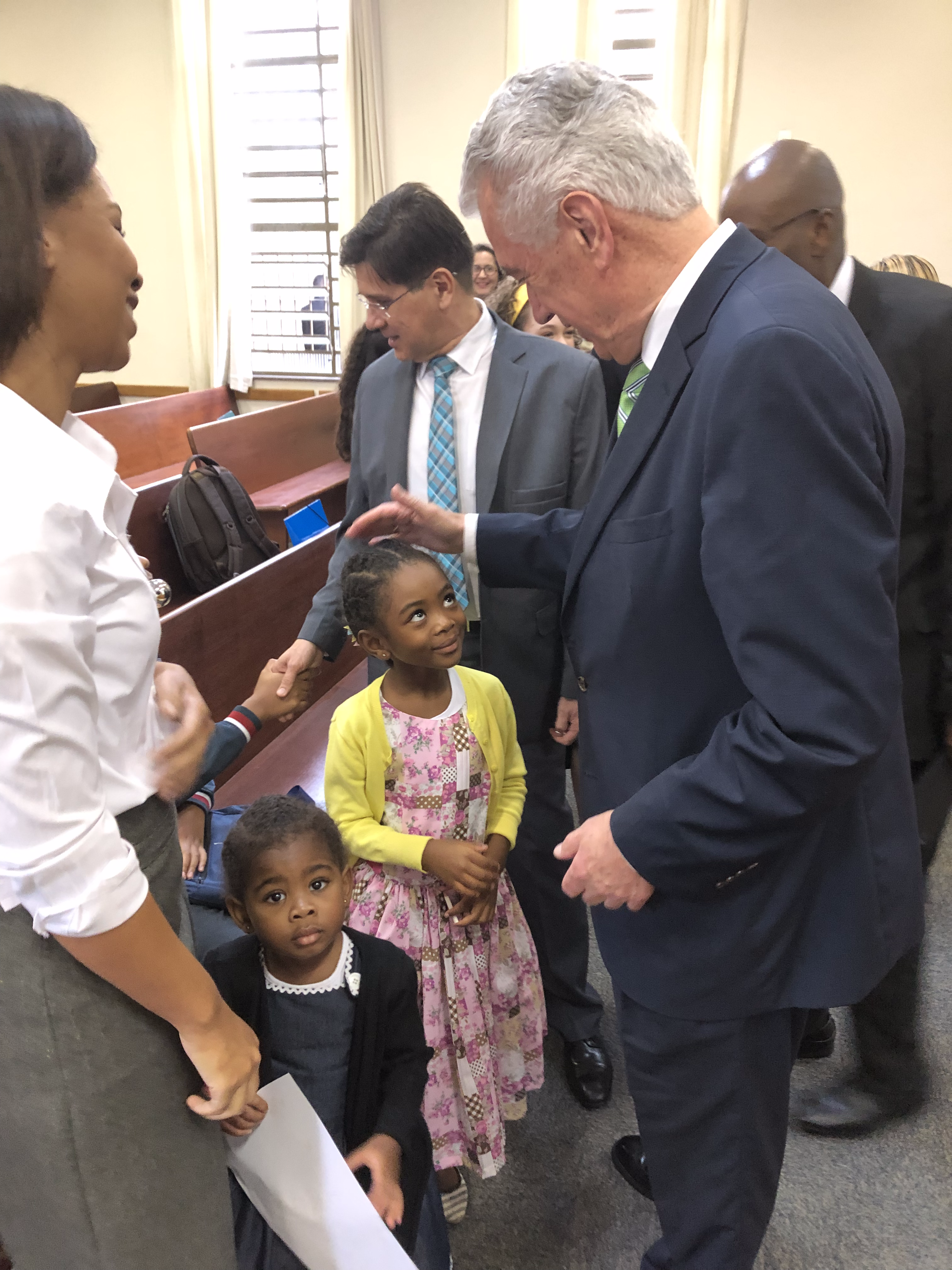 Elder Dieter F. Uchtdorf of the Quorum of the Twelve Apostles greets Melissa de Souza Sabino Ferreira, the daughter of President Paulo Ferreira of the Sao Paulo Brazil Jaraguá Stake, after meetings on Sunday, Feb. 17. Standing nearby is her younger sister, Micaela de Souza Sabino Ferreira, and her mother, Regiane de Souza Sabino Ferreira, left.
