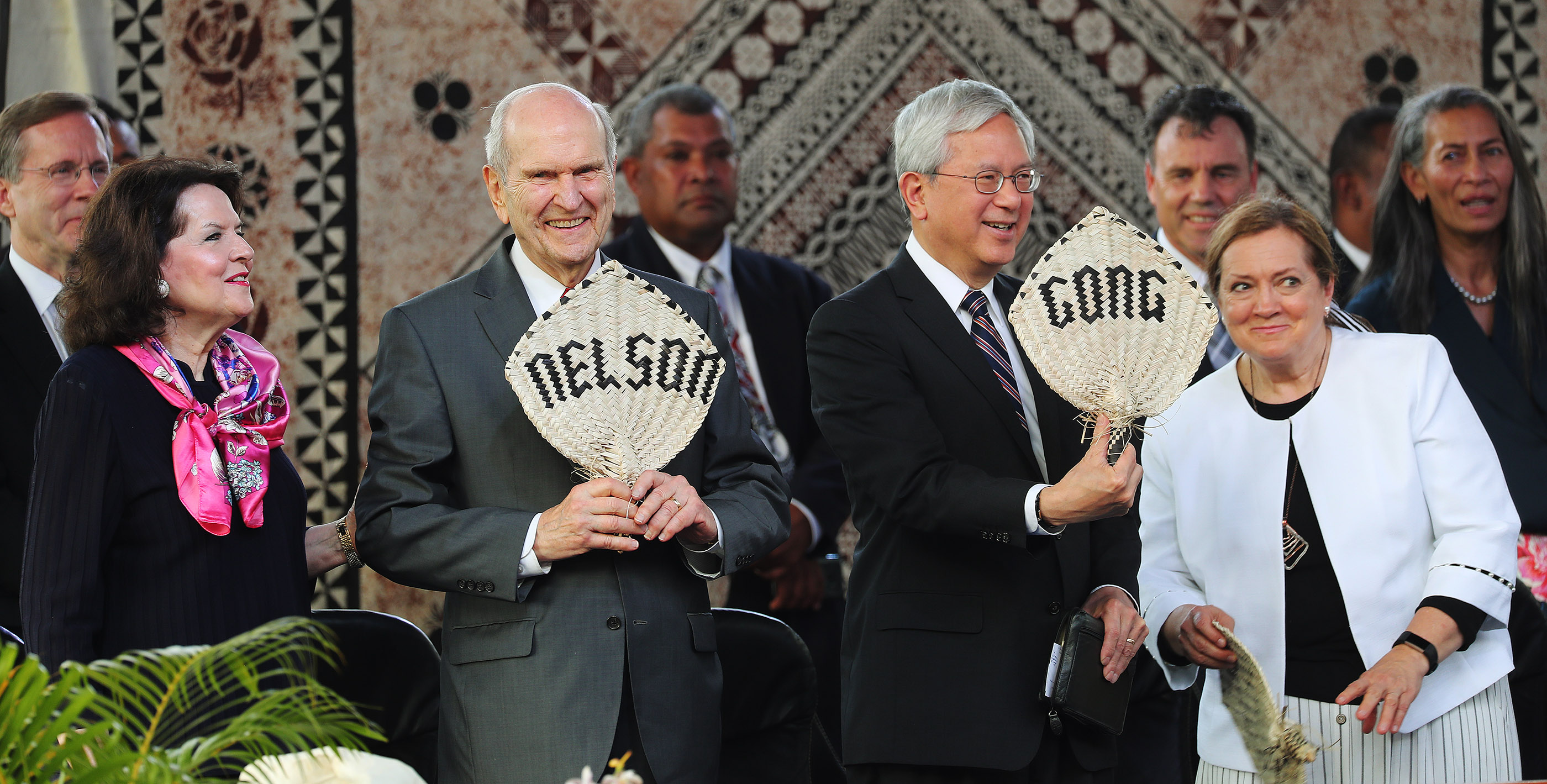 President Russell M. Nelson of The Church of Jesus Christ of Latter-day Saints and his wife, Sister Wendy Nelson, and Elder Elder Gerrit W. Gong, of the Quorum of the Twelve Apostles and his wife, Sister Susan Gong, hold fans with their names on them at a devotional at Ratu Cakobau Park stadium in Nausori, Fiji, on May 22, 2019.