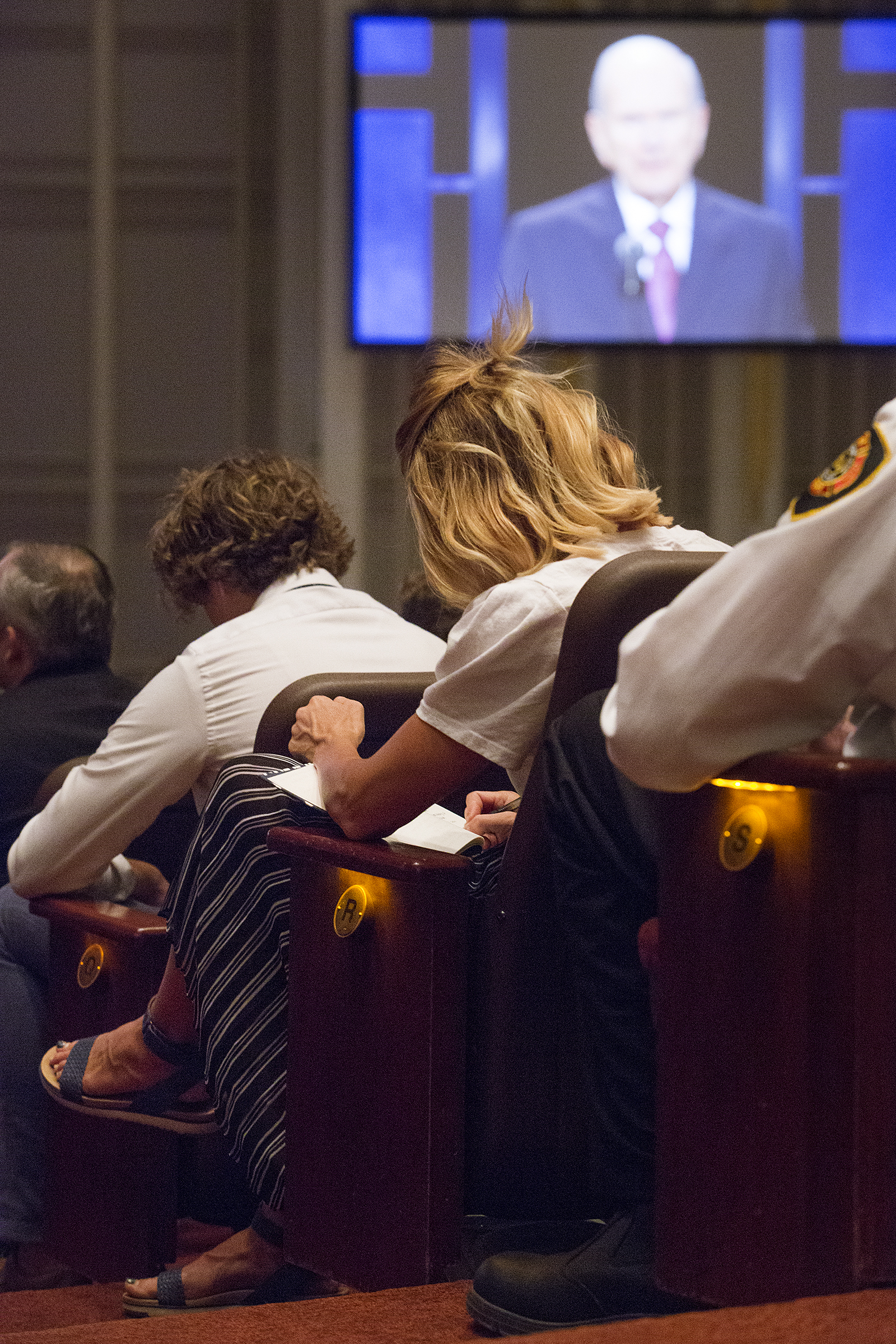 An attendee takes notes as President Russell M. Nelson speaks during the Worldwide Youth Devotional at the Conference Center in Salt Lake City on Sunday, June 3, 2018.