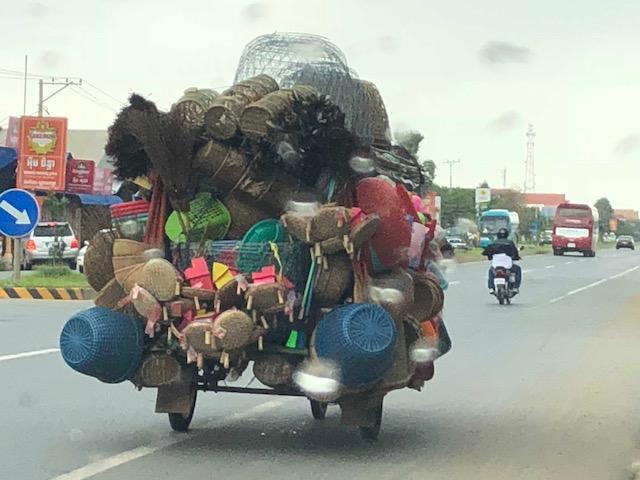 A Tuk Tuk driver transporting goods.