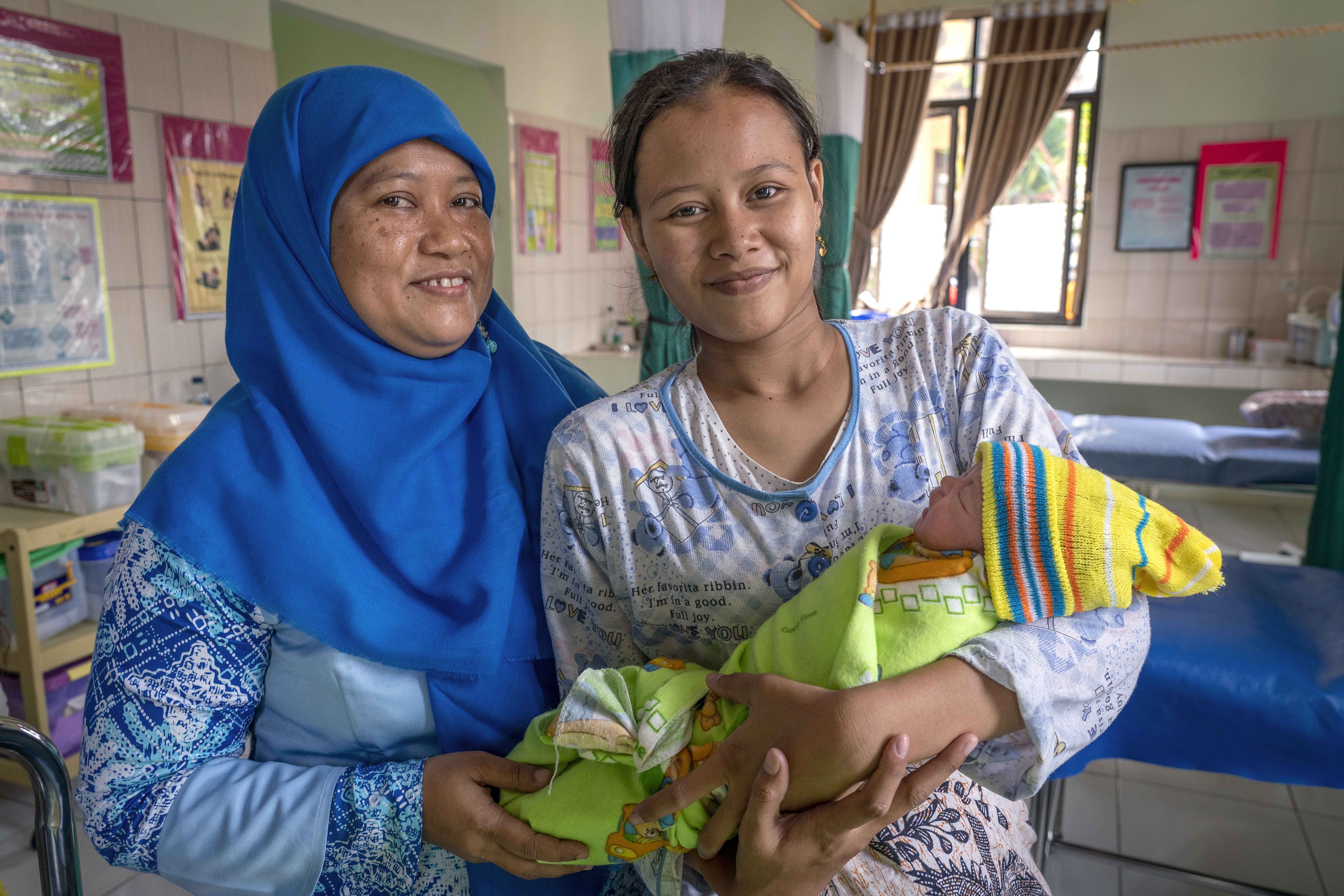 A nurse in Banyumas, Indonesia, stands next to a new mother. In 2018, nurses in this birthing center completed a Helping Babies Breathe course run by LDS Charities facilitators.