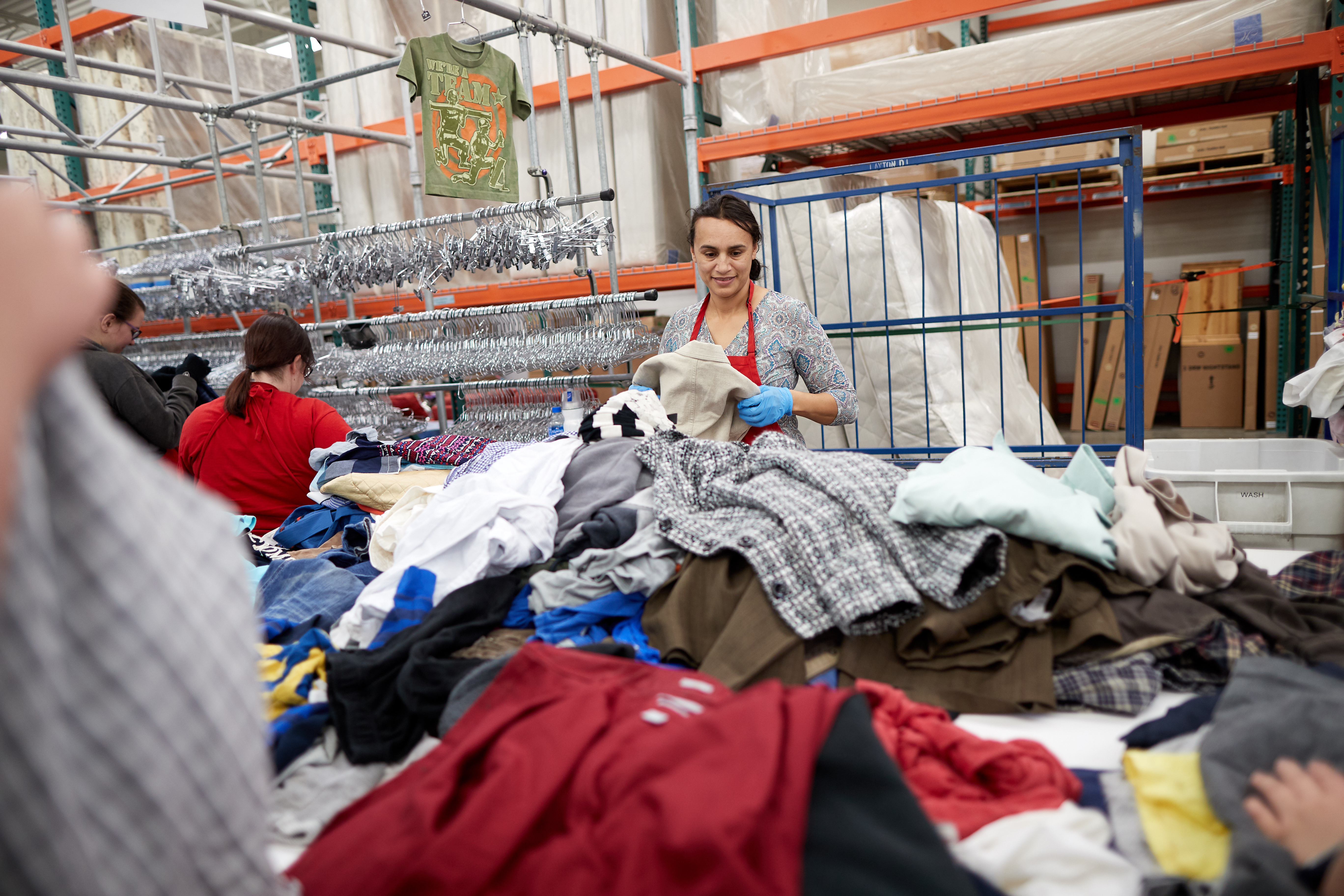 An associate in the job-training program sorts clothes at a Deseret Industries store.