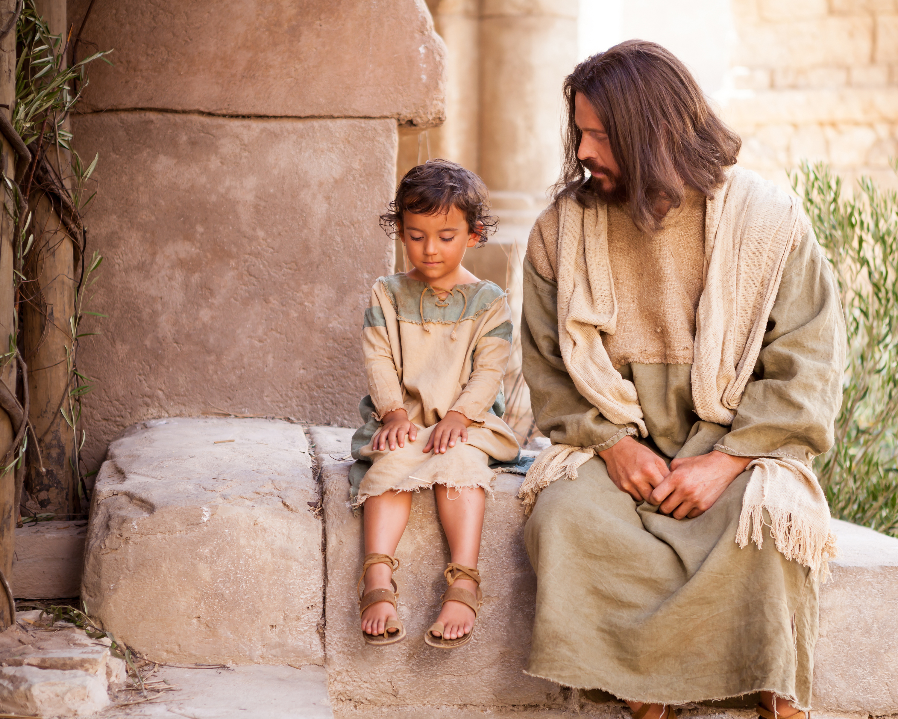 """Jesus Christ sits with a young child while teaching that we must """"become as little children"""" in this image from the Bible Videos series."""