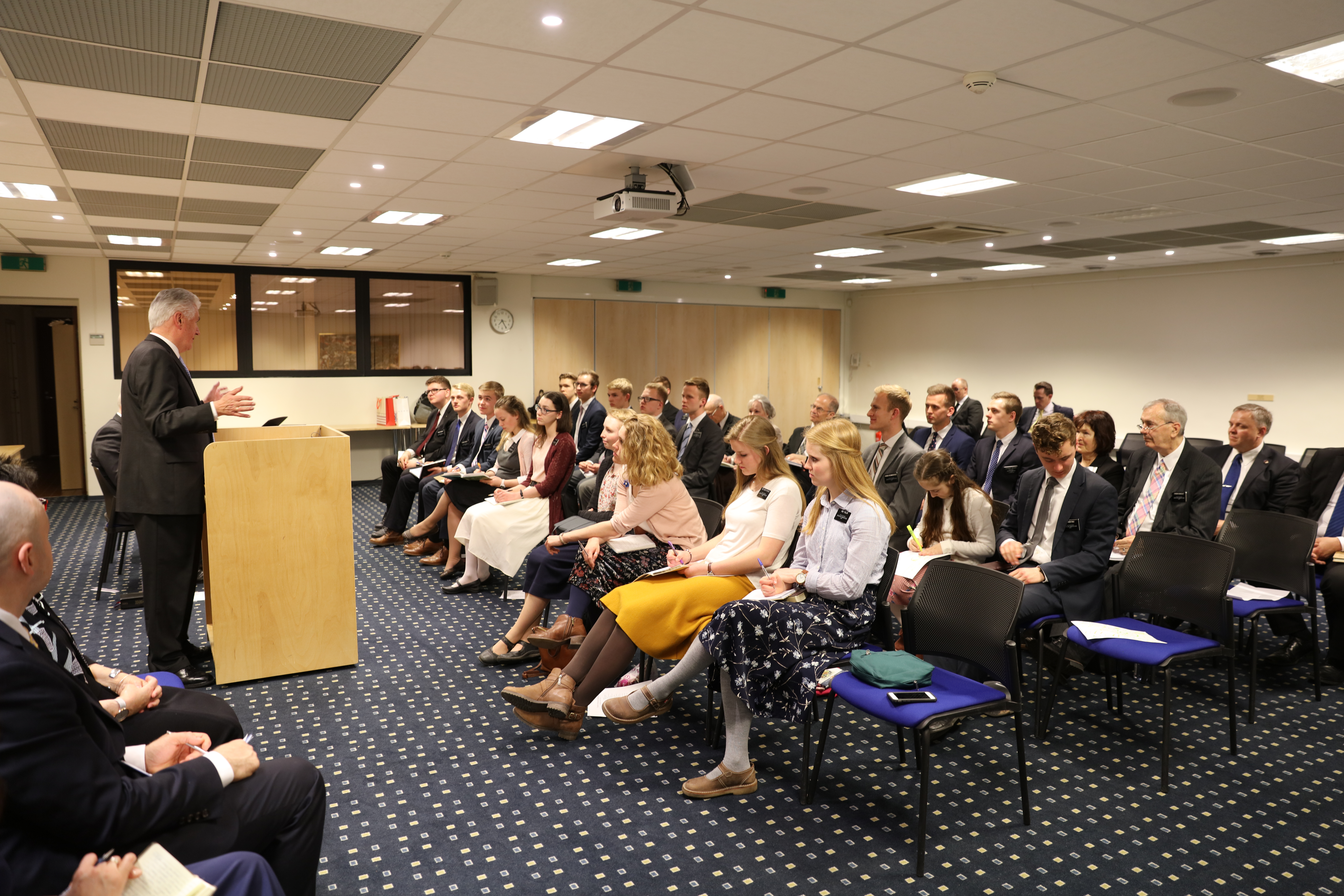 Elder Dieter F. Uchtdorf of the Quorum of the Twelve Apostles, standing at the podium, speaks to missionaries of the Baltic Mission in an April 28, 2018, meeting in Tallinn, Estonia.