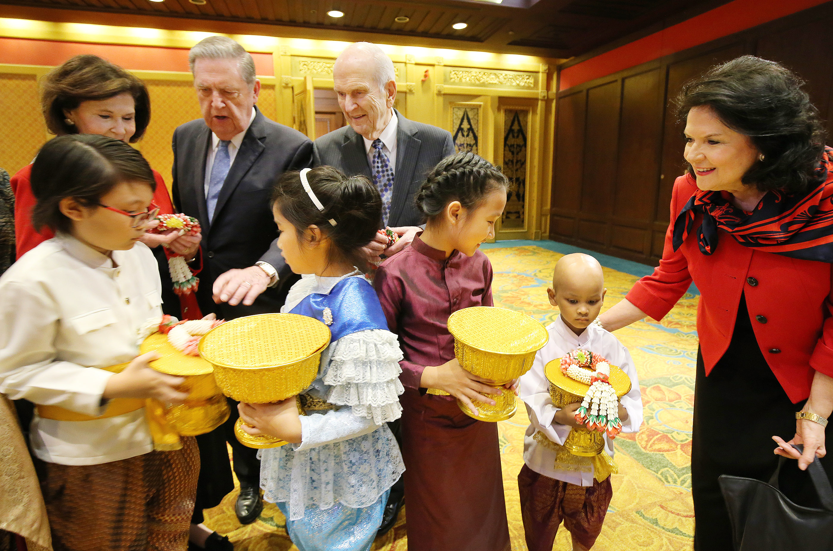 President Russell M. Nelson and his wife, Sister Wendy Watson Nelson, and Elder Jeffrey R. Holland, Quorum of the Twelve Apostles, and Sister Patricia Holland are greeted and given flowers by Primary children in Bangkok, Thailand, on Friday, April 20, 2018.