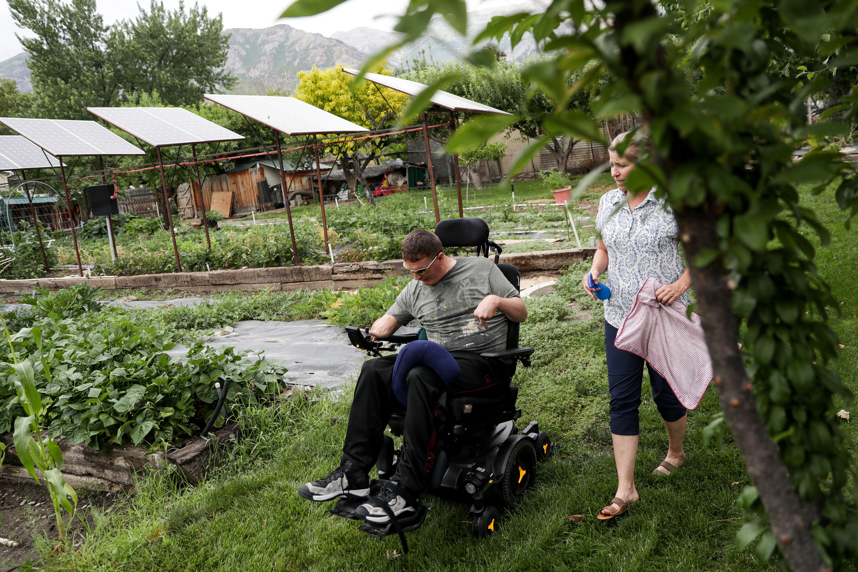 Orin Voorheis drives his motorized wheelchair, with caregiver Wendy Tobey close behind, in the garden outside his home in Pleasant Grove, Utah, on Tuesday, July 10, 2018.