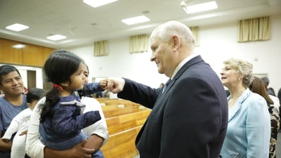 Elder Dale G. Renlund fist bumps a young girl while greeting her family following a devotional for women in Antofagasta, Chile, on Feb. 15, 2019. His wife, Sister Ruth Renlund, is also pictured to his right.