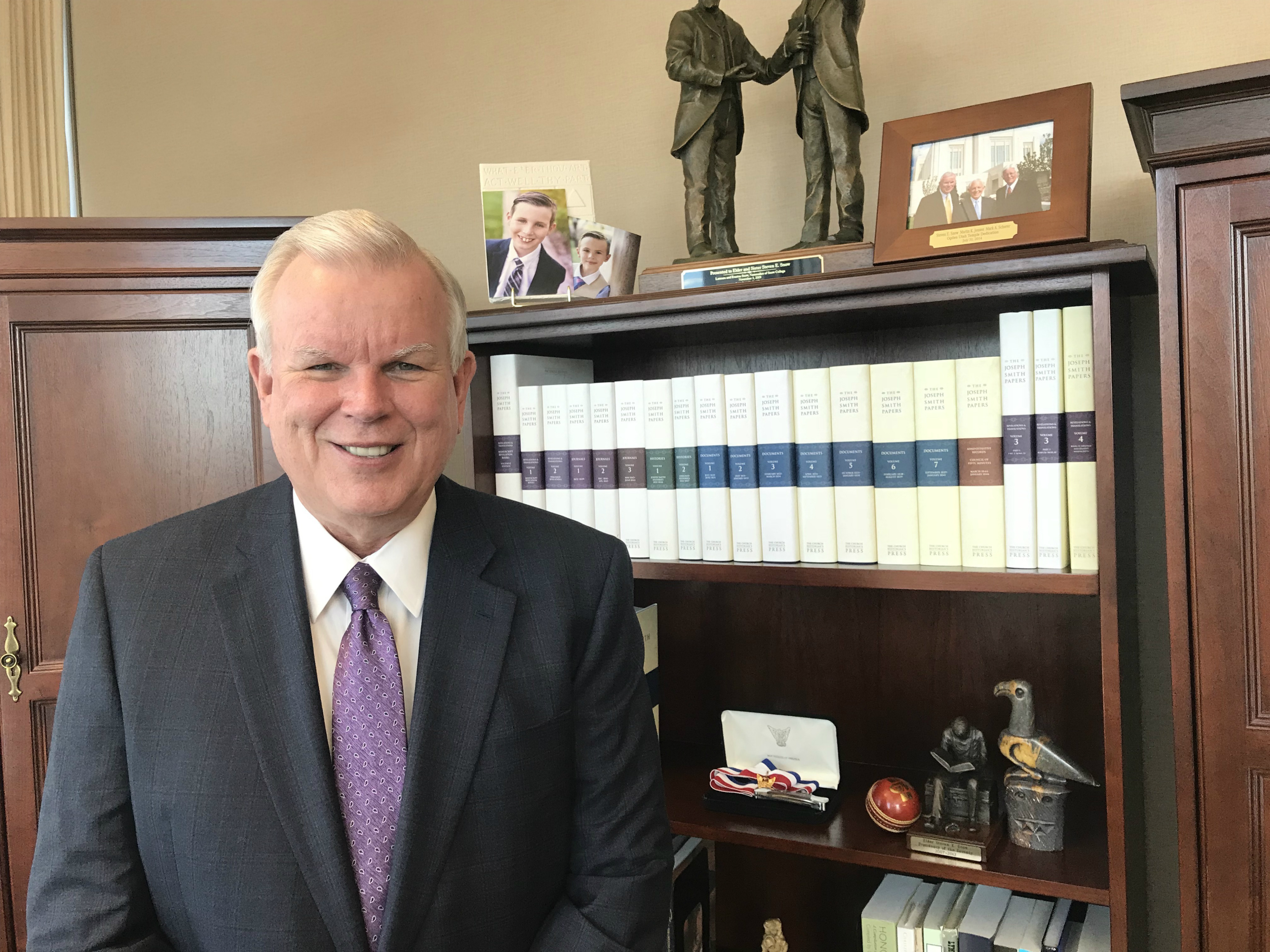 Elder Steven E. Snow, a General Authority Seventy and church historian and recorder, stands next to a bookshelf in his Church History Library office containing volumes of the Joseph Smith Papers project, published over the last decade, on Oct. 23, 2018.