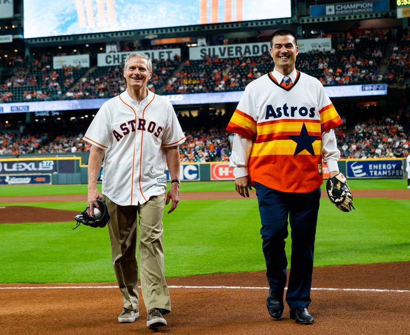 Elder David A. Bednar and President Jeremy Guthrie return from the successful ceremonial first pitch.