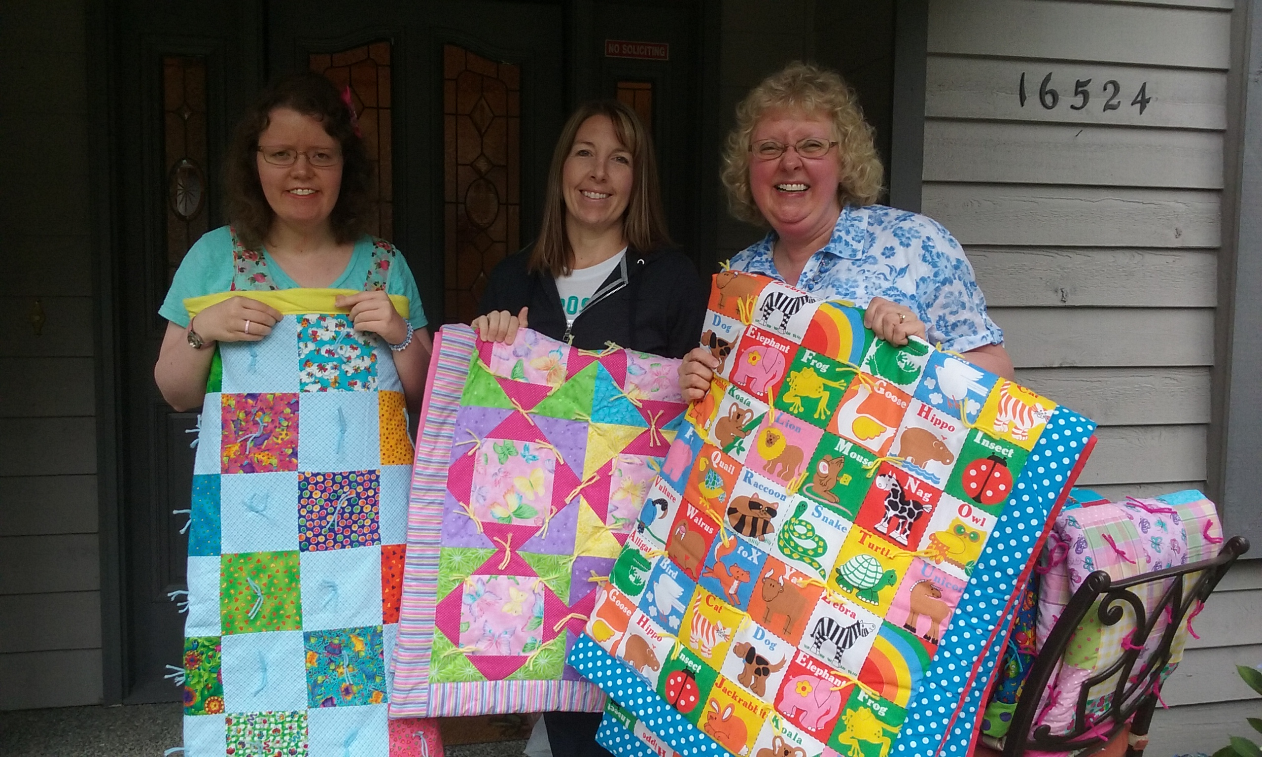 "Elizabeth Thomas, right, and her daughter Rebeca Thomas, left, deliver quilts made by the ""Helping Hands, Loving Hearts Sew for Community"" service group to the Wishing Well, clothing bank for foster kids in Pierce County, WA."