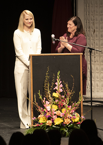 Guest speaker Elizabeth Smart, left, stands with Melinda Huish, right, at an evening event during the 2019 Associated Ministries Interfaith Women's Conference.