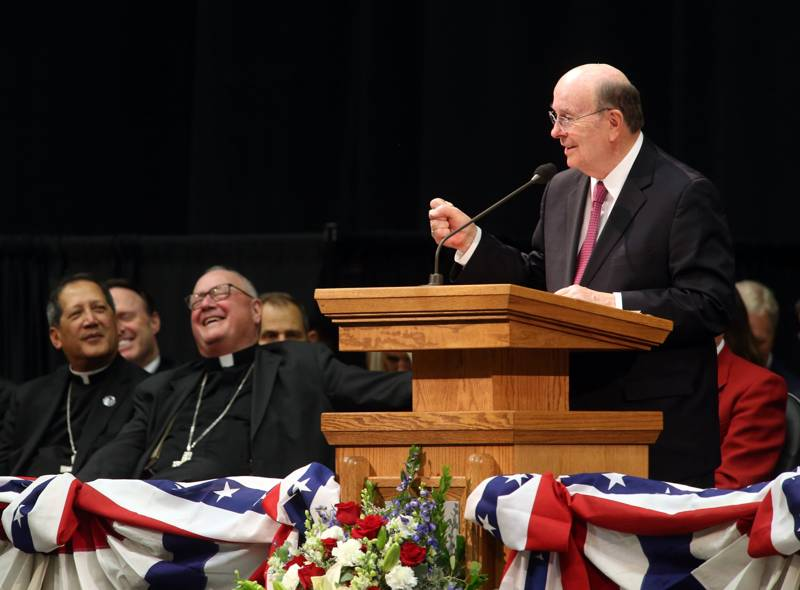 Elder Quentin L. Cook of the Quorum of the Twelve Apostles inserts humor into his introduction of Timothy Cardinal Dolan, the Catholic archbishop of New York, during the patriotic service for the America's Freedom Festival at Provo at Utah Valley University in Orem, Utah, on Sunday, June 30, 2019.