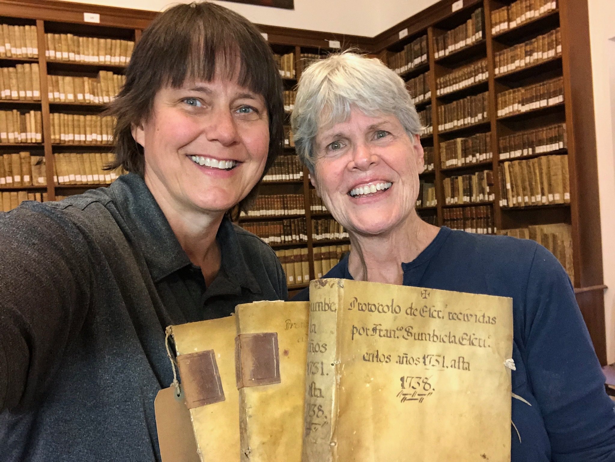 Senior missionaries Sister Klafke and Sister Rife hold the last three books from the 18th-century selection of the archive. The two friends are currently serving a records preservation mission in Spain.