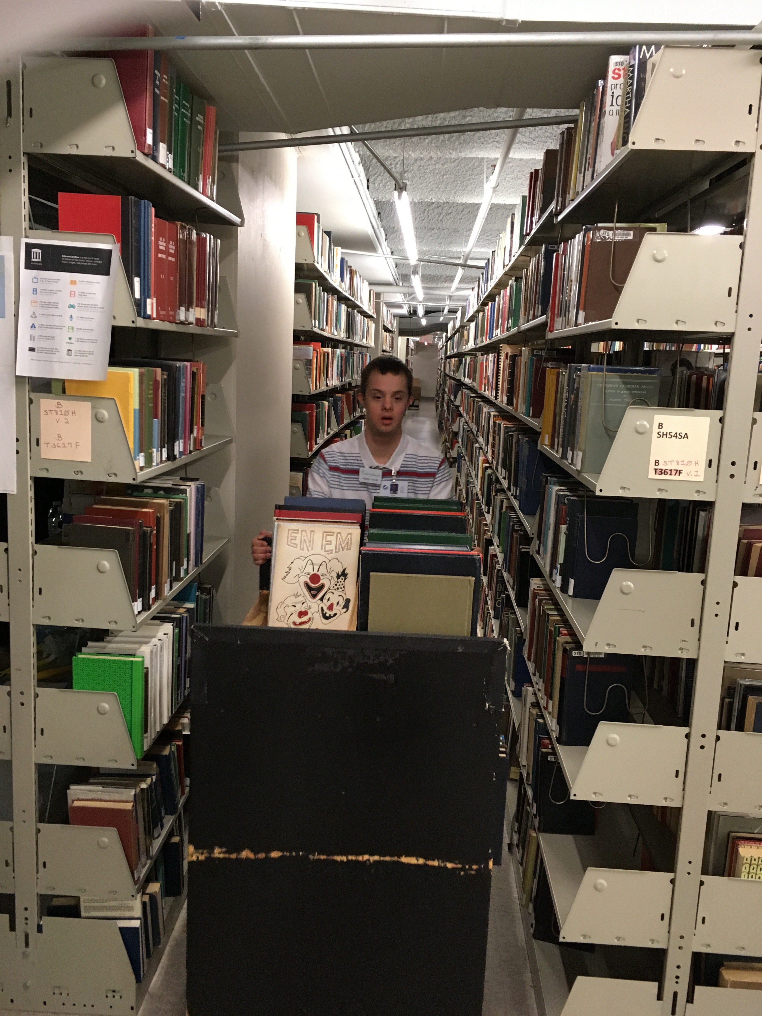 Russell Taylor, who has Downs syndrome, finds books to scan at the Allen County Public Library in Fort Wayne, Indiana, while serving a records preservation mission with his parents.