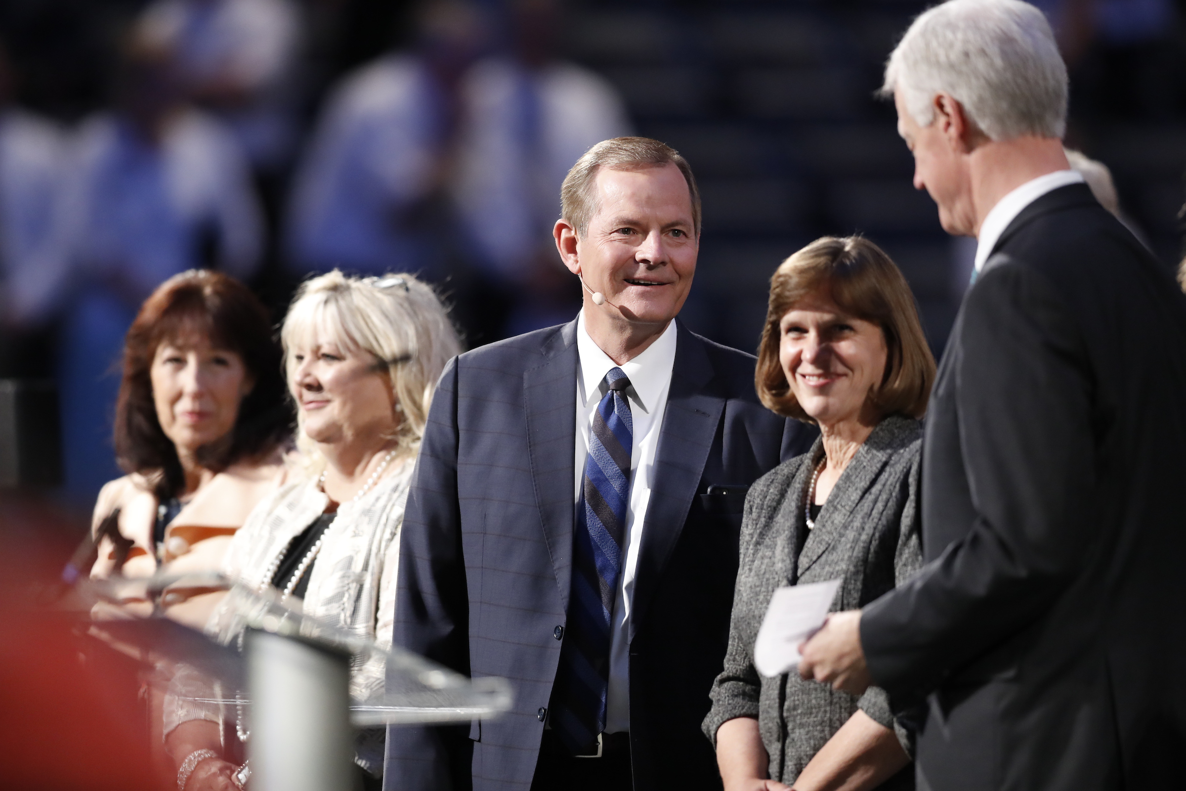 Elder Gary E. Stevenson of the Quorum of the Twelve Apostles, center, and his wife, Sister Lesa Stevenson, left, on the stand with BYU President Kevin J Worthen and his wife, Sister Peggy Worthen, prior to Elder Stevenson speaking at a devotional during BYU Education Week in the Marriott Center on Aug. 20, 2019.