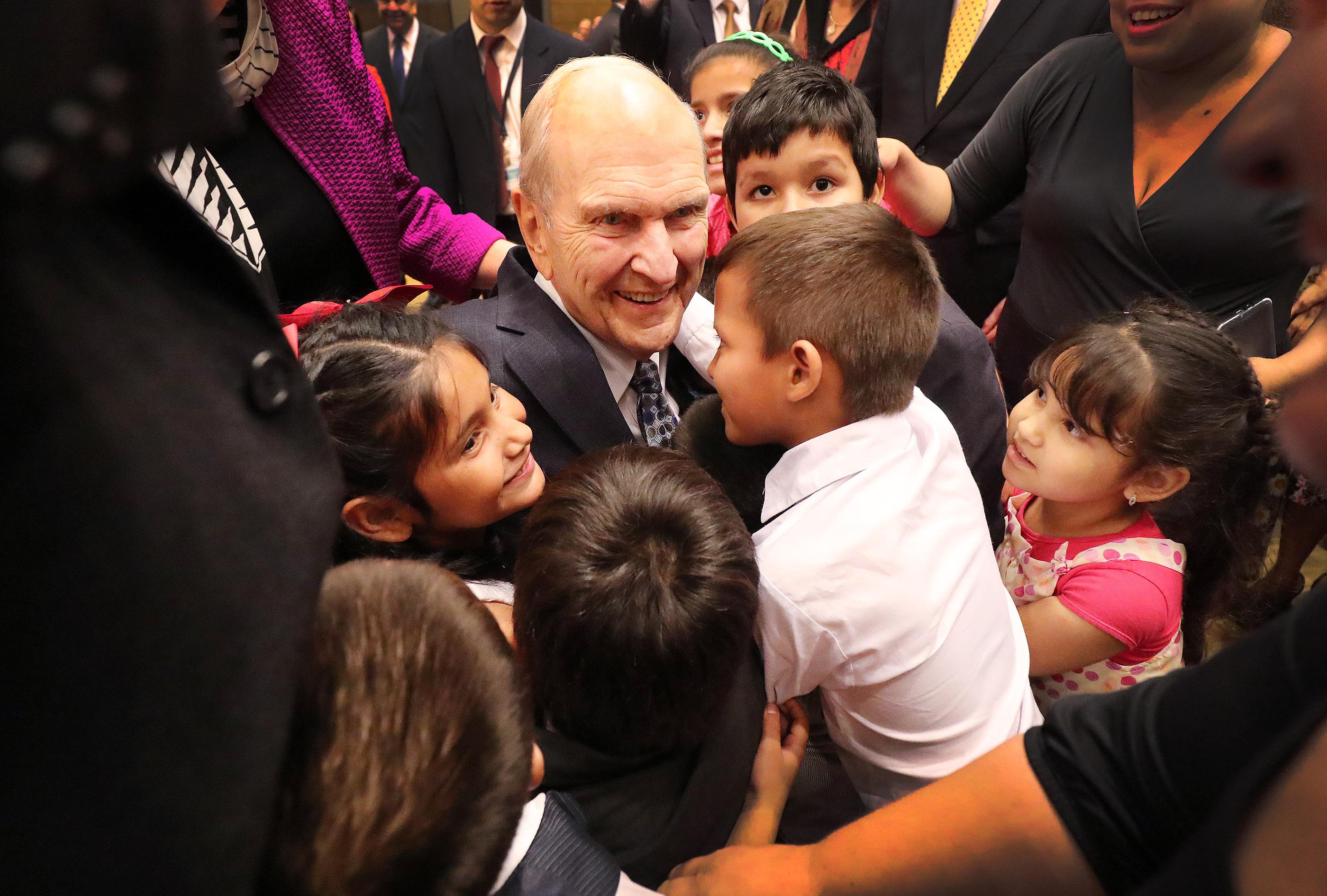 El presidente Russell M. Nelson, de La Iglesia de Jesucristo de los Santos de los Últimos Días, abraza a los niños después de un devocional en Asunción, Paraguay, el lunes 22 de octubre de 2018.