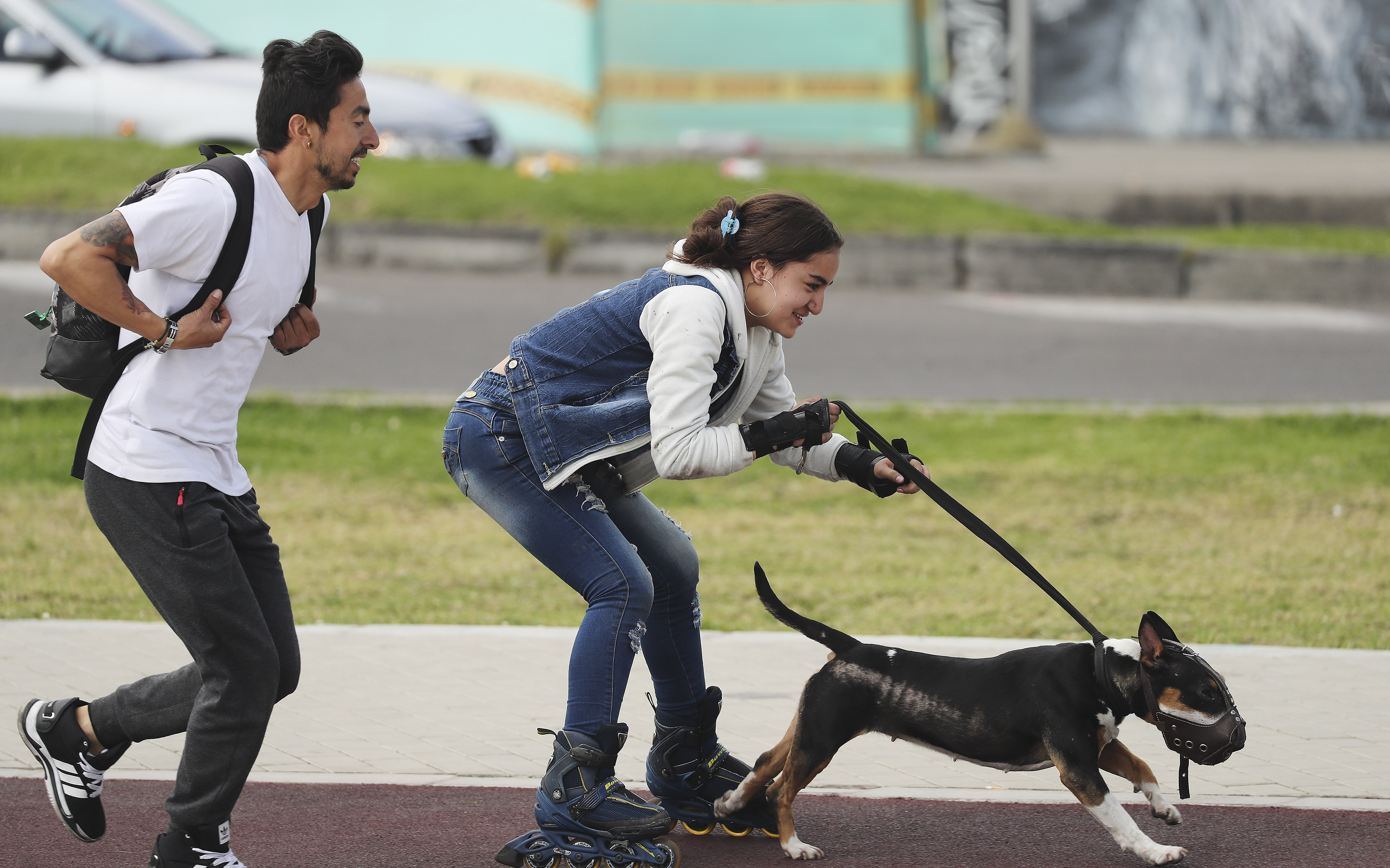 A couple run with their dog in Bogota, Colombia, on Sunday, Aug. 25, 2019.